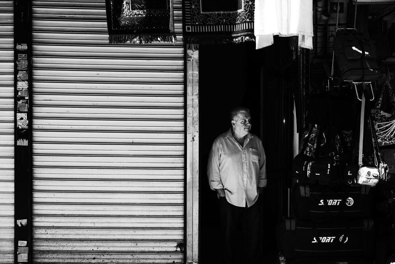 Peek-a-boo! Blackandwhite From The Dark Fujifilm Monochrome One Man Only Peek-a-Boo! Real People Rugs Seller Senior Men Streetphotography