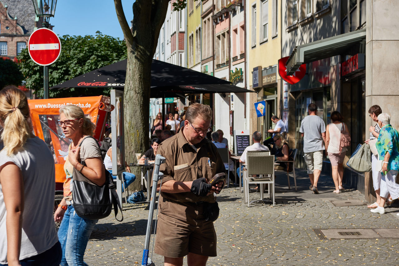 DUESSELDORF, GERMANY - AUGUST 17, 2016: Unidentified parcel service clerk checks data on his mobile device in the Altstadt of Duesseldorf Altstadt Atmosphere Bar Blu Sky City Life City Street Daytime Düsseldof High Resolution Lifestyles Men Music NRW Outdoors People R Relaxing Restaurant Rheinland-Pfalz  Rhine Promna S Shopping Tourism Travel Destinaton Young Women