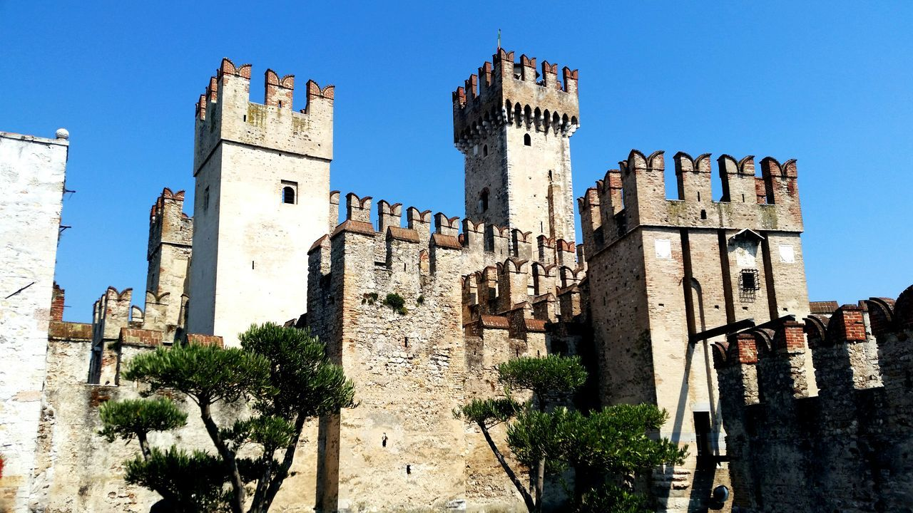 architecture, low angle view, building exterior, history, castle, day, built structure, clear sky, outdoors, no people, travel destinations, tree, blue, sky, city
