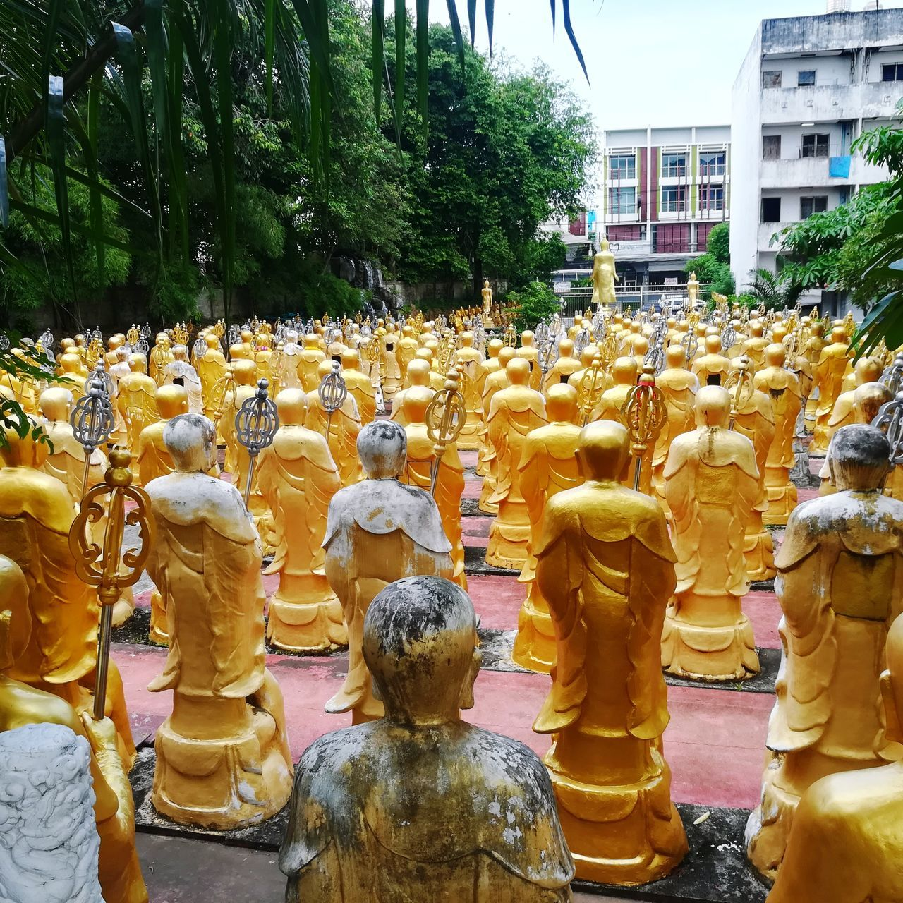 in a row, statue, sculpture, yellow, human representation, day, outdoors, building exterior, tree, no people