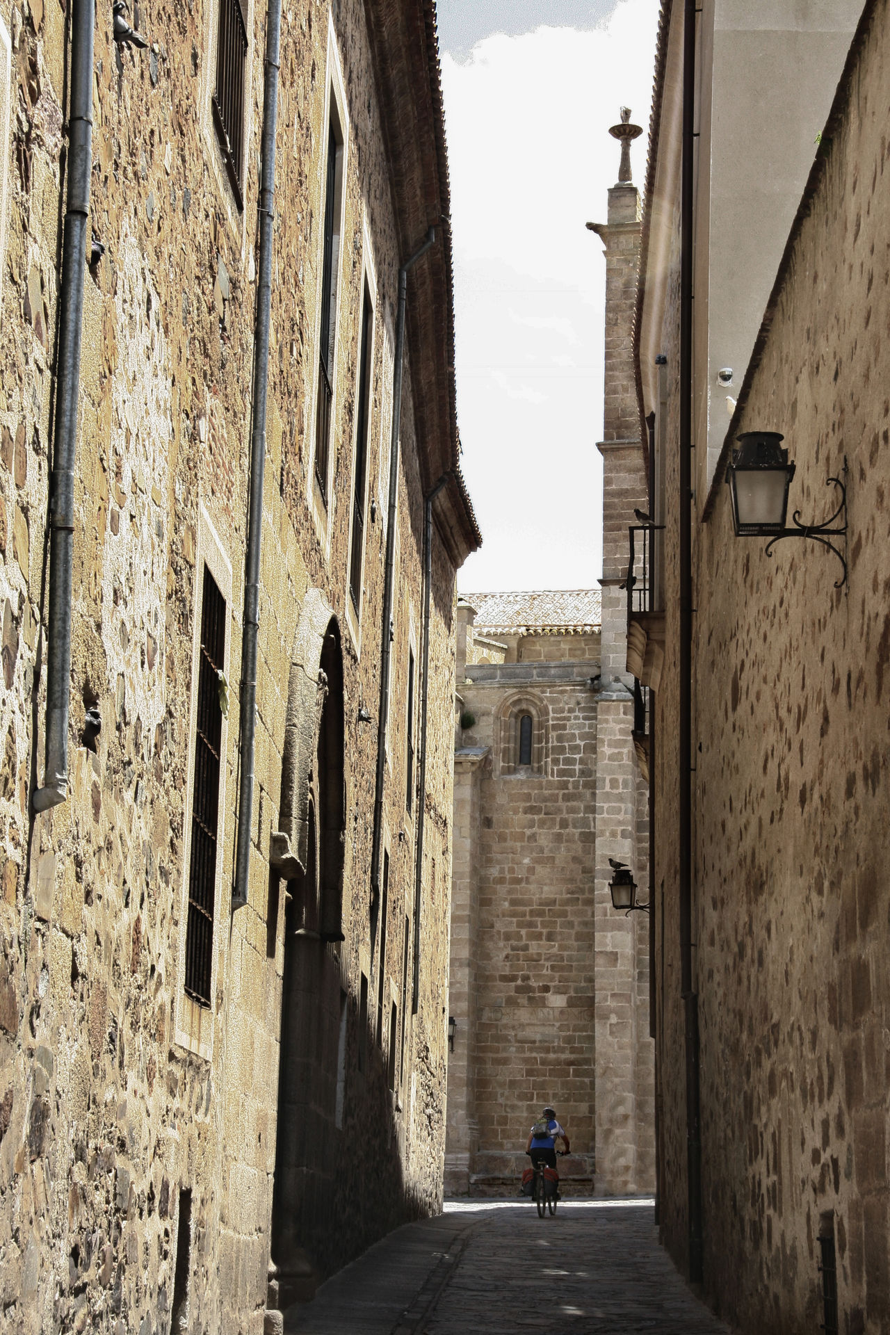 Biker crossing through the narrow streets of Caceres Old Town, Spain Architecture Building Exterior Built Structure City Day Men One Person Outdoors Real People Sky The Way Forward