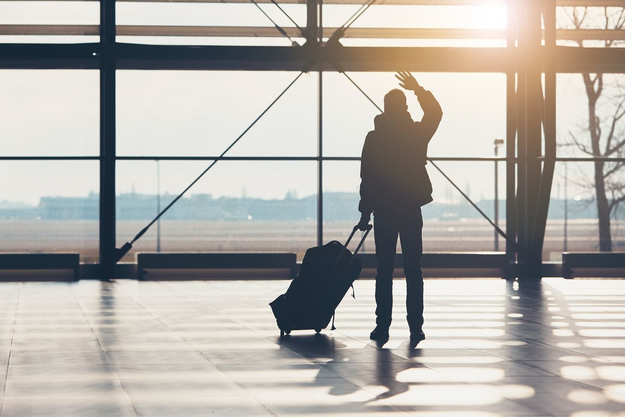 Saying goodbye at the airport. Silhouette of the traveler waves his hand. Airport Airport Terminal Boarding Farewell Flying Goodbye Greeting Journey Leaving Luggage Man Passenger People Silhouette Suitcase Sunlight Sunshine Tourism Tourist Transportation Travel Traveler Trip Waving Welcome