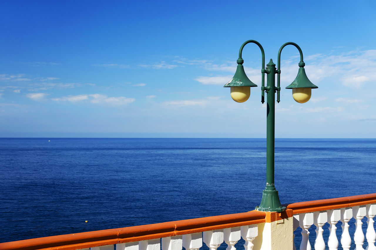 Lighting Equipment On Railing By Sea Against Sky