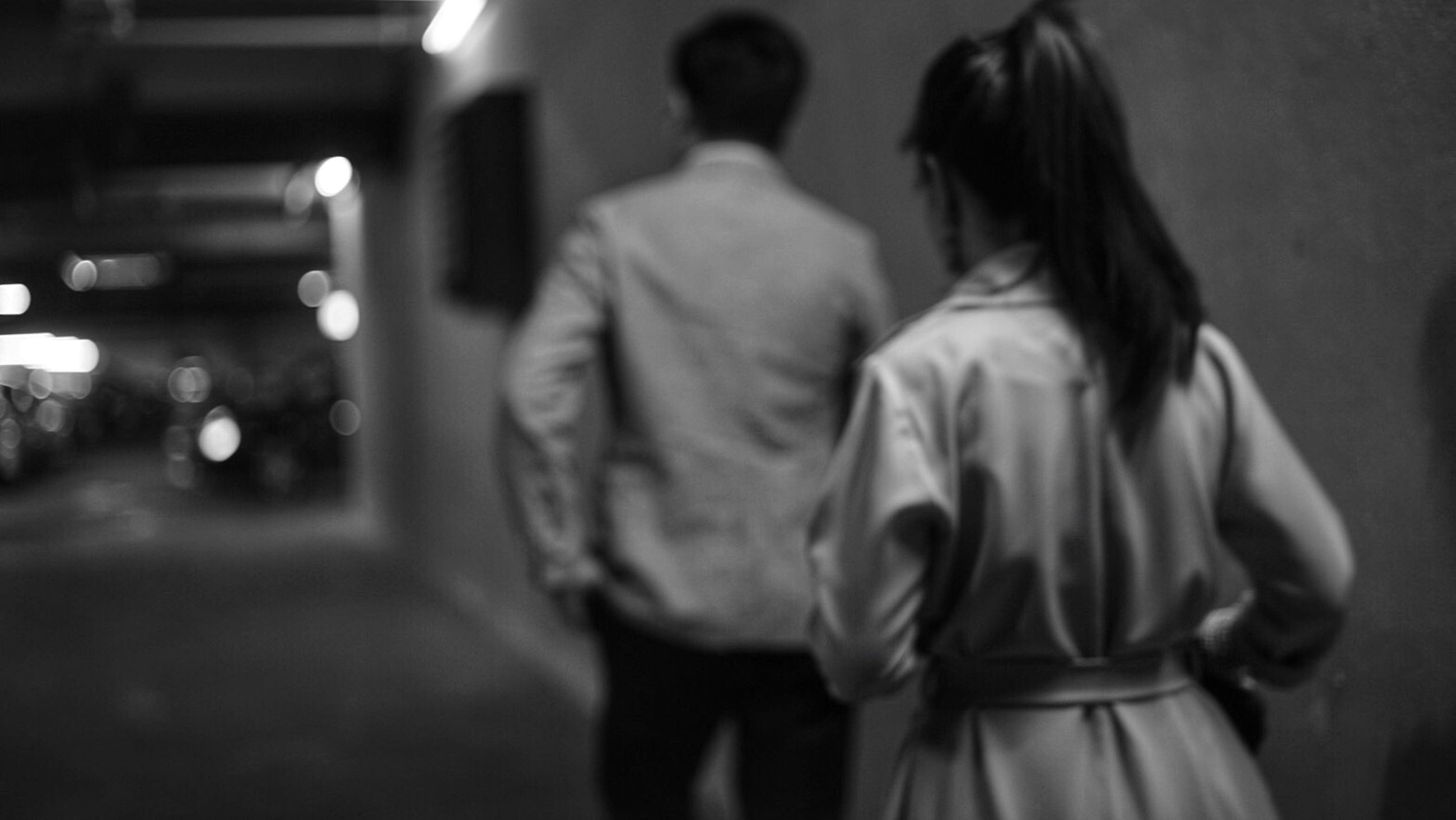 lifestyles, rear view, night, leisure activity, men, focus on foreground, illuminated, casual clothing, indoors, standing, person, street, full length, selective focus, walking, incidental people, holding