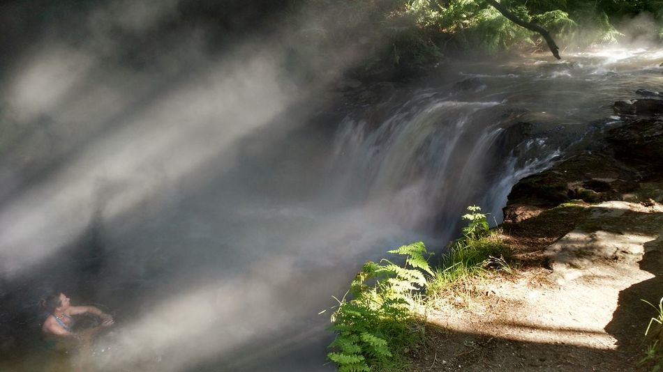 A girl Luxuriates in a Thermal Stream as Steam rises . Waterfall Kerosene Creek Nature Power In Nature Flowing Water Idyllic Tranquility Swimming Hot Spring
