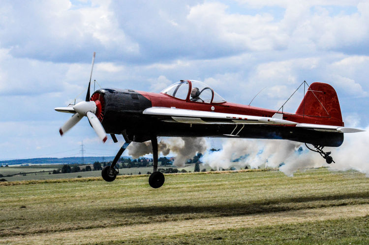 Airplane Air Vehicle Old-fashioned Military Airplane Aerospace Industry Outdoors Propeller Airplane Sky Red Airshow Gasoline Smoke
