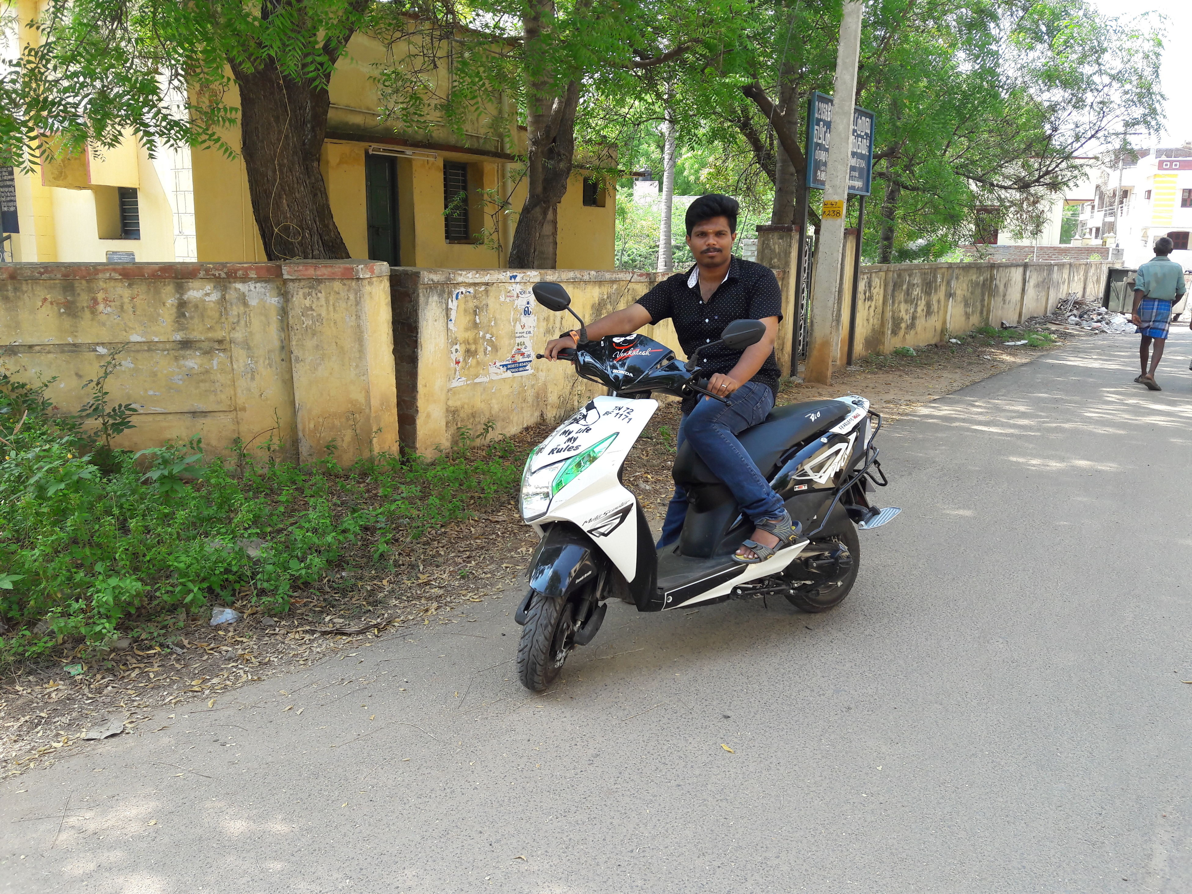full length, motorcycle, transportation, one person, mode of transport, day, leisure activity, riding, outdoors, land vehicle, tree, sitting, adults only, real people, building exterior, young adult, helmet, adult, one man only, people, headwear, only men