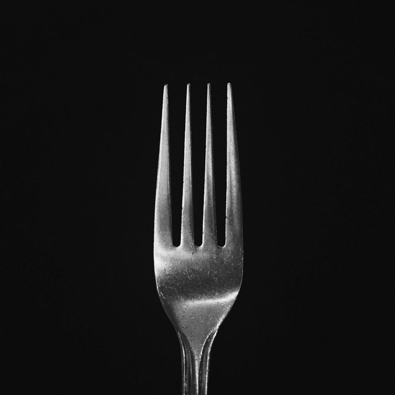 Close-Up Of Fork Against Black Background