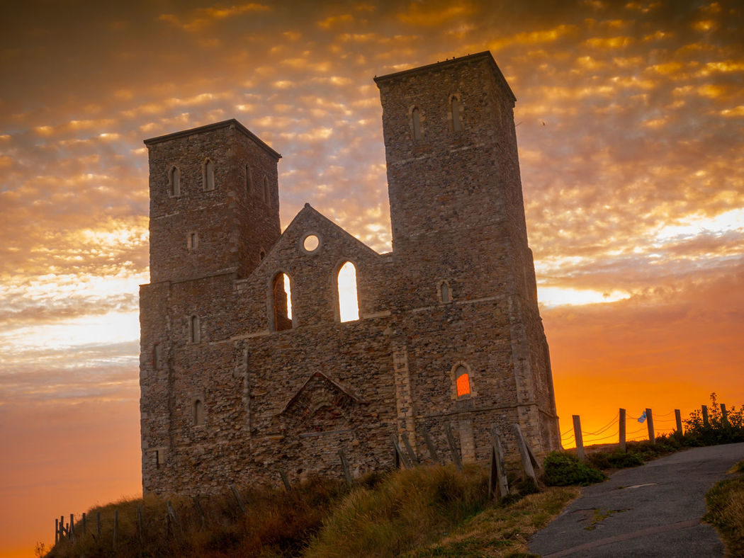 Reculver is a village and coastal resort about 3 miles (5 km) east of Herne Bay in south-east England, in a ward of the same name, in the City of Canterbury district of Kent. It once occupied a strategic location at the north-western end of the Wantsum Channel, a sea lane that separated the Isle of Thanet and the Kent mainland until the late Middle Ages. This led the Romans to build a small fort there at the time of their conquest of Britain in 43 AD, and, starting late in the 2nd century, they built a larger fort, or castrum, called Regulbium, which later became one of the chain of Saxon Shore forts. The military connection resumed in the Second World War, when the sea off Reculver was used for testing Barnes Wallis's bouncing bombs. Building Exterior City Dramatic Sky Fantasy Kent Medieval Mountain Nature Night No People Old Outdoors Reculver Reculver Towers Sunset Travel Travel Destinations Vivid International