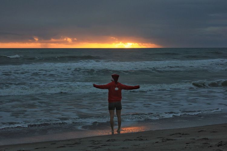 Celebrating sunrise Cocoa Beach, Florida Sunrise And Clouds Real People One Person Horizon Over Water Arms Outstretched Young Adult Surfing Santa Santa Hat Surfing Santas