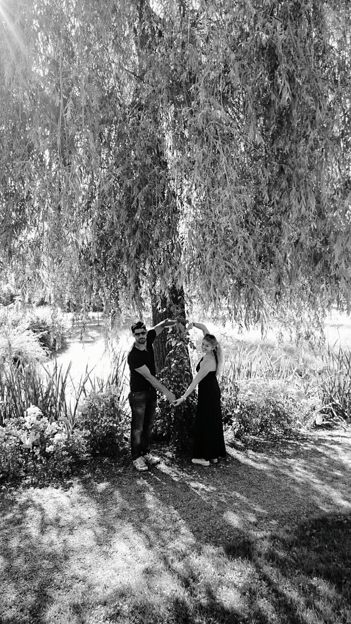 two people, real people, tree, nature, men, togetherness, leisure activity, standing, day, women, full length, outdoors, lifestyles, growth, grass, water, beauty in nature, people