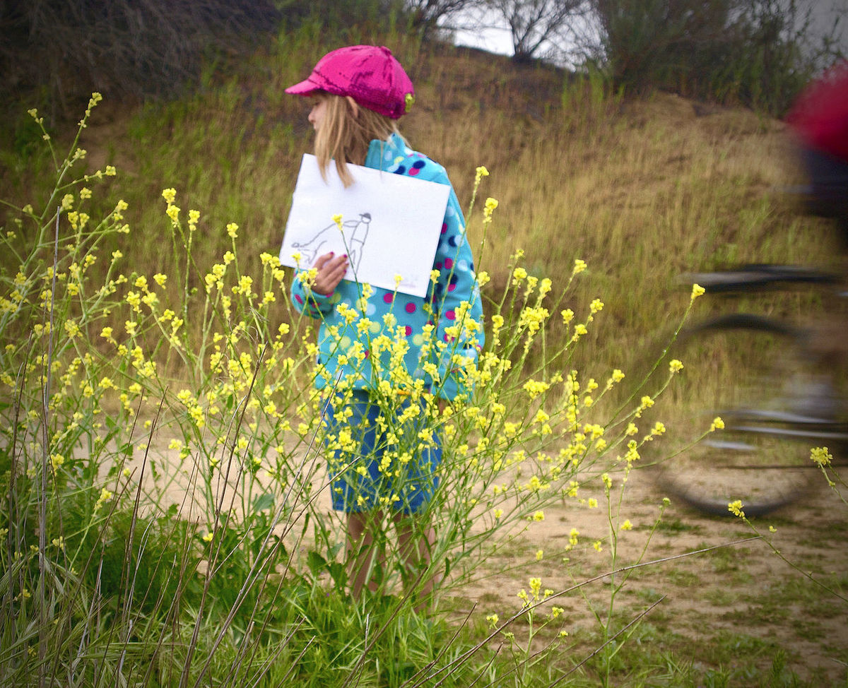 Bicyclist Blurred Motion Casual Clothing Diverted Attention Holding A Drawing Landscape Outdoors Pink Hat Wild Mustard Plants Yellow Flowers Young Girl