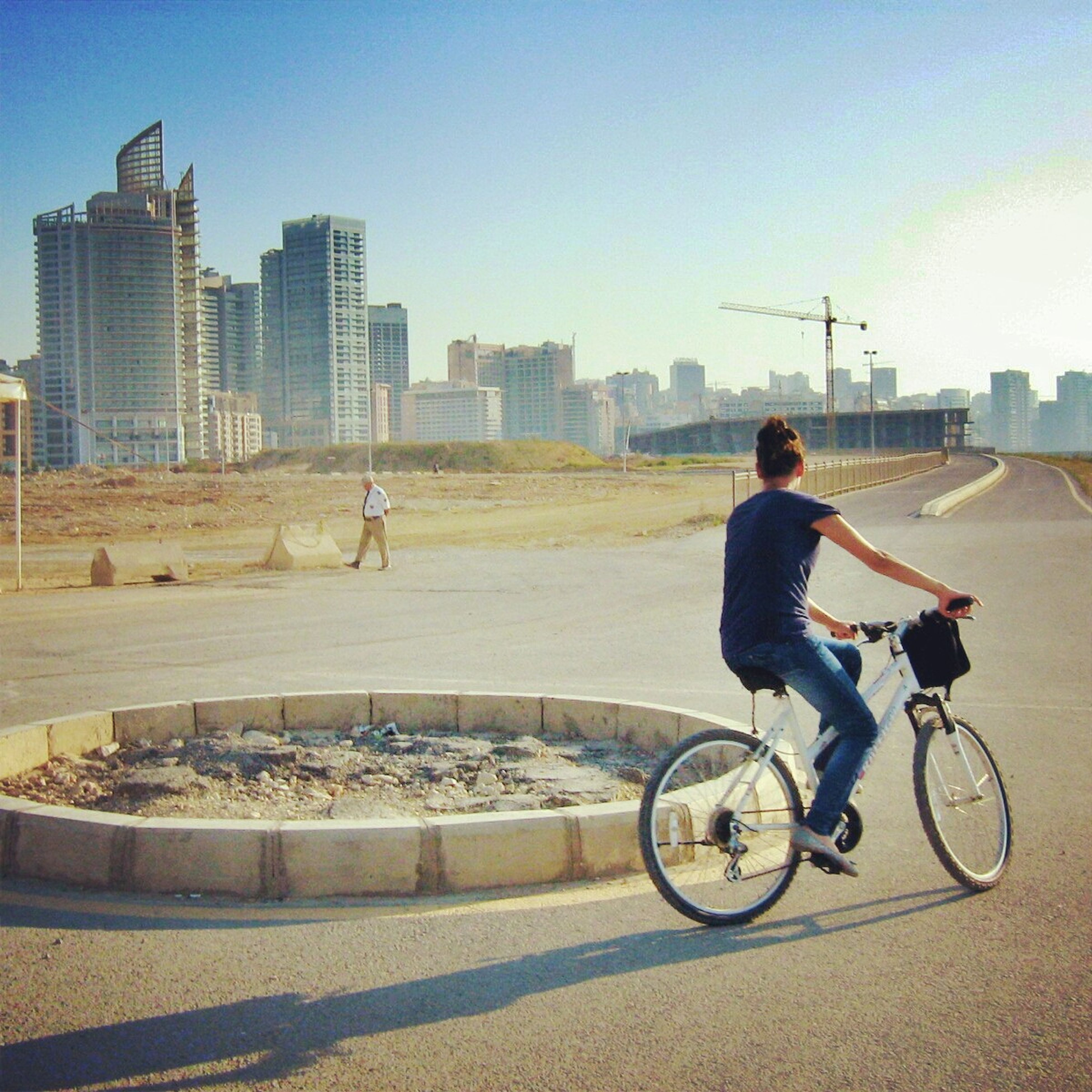 bicycle, building exterior, architecture, built structure, full length, transportation, lifestyles, city, land vehicle, mode of transport, riding, leisure activity, clear sky, casual clothing, side view, men, young adult, street