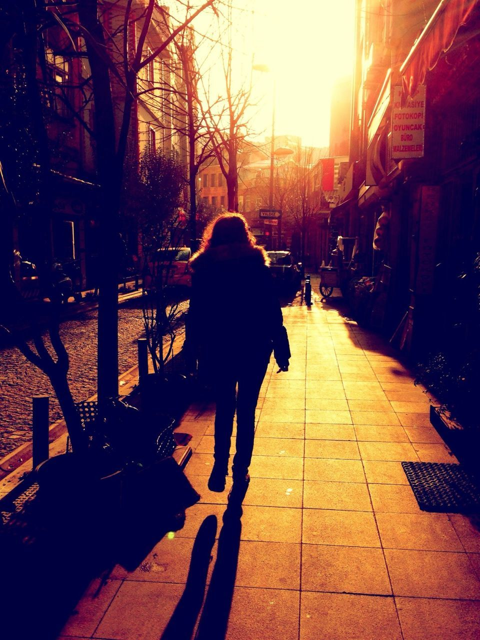 Rear View Of Woman Walking On Sidewalk During Sunset
