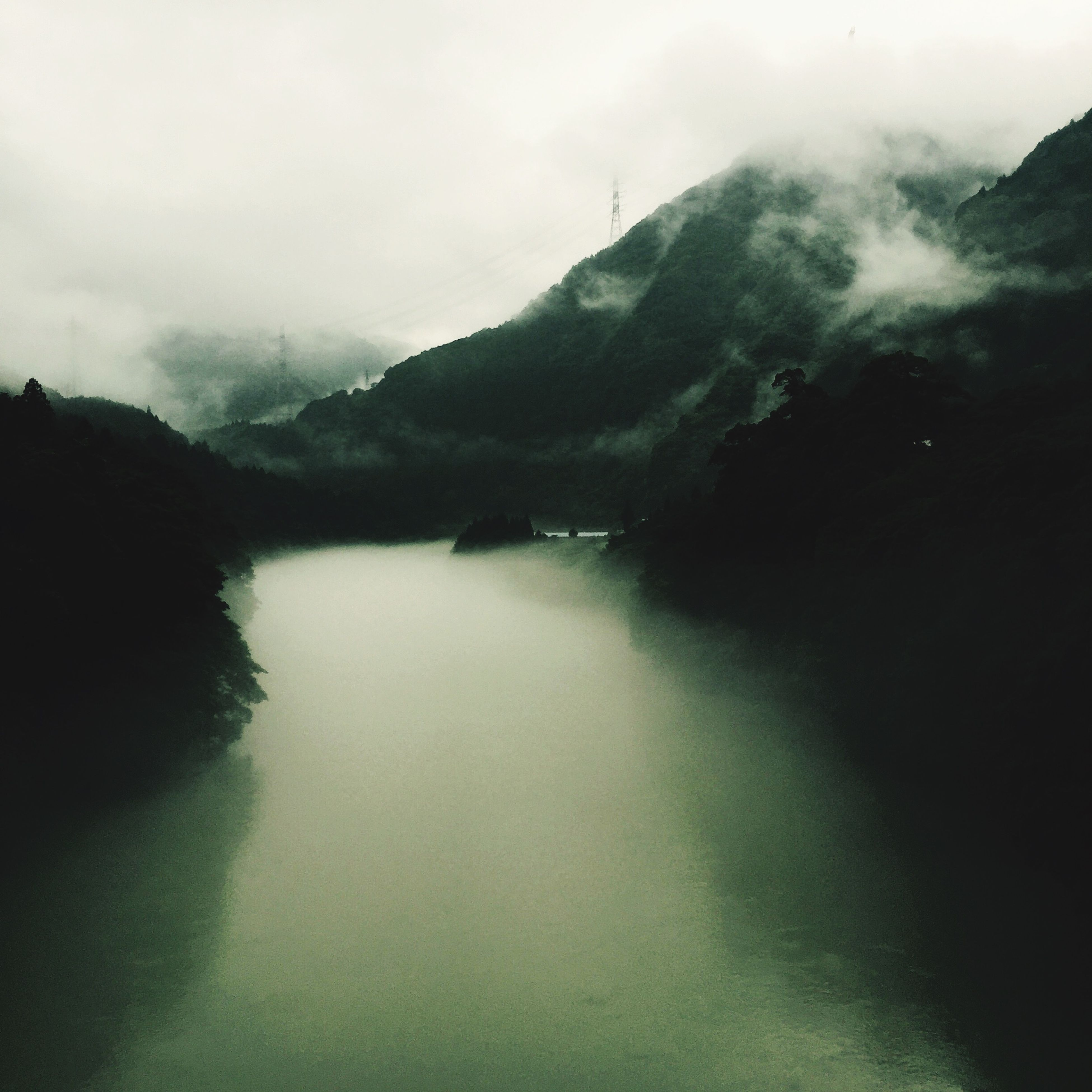 mountain, tranquil scene, tranquility, scenics, water, mountain range, beauty in nature, lake, nature, fog, sky, waterfront, non-urban scene, idyllic, river, weather, reflection, landscape, outdoors, remote