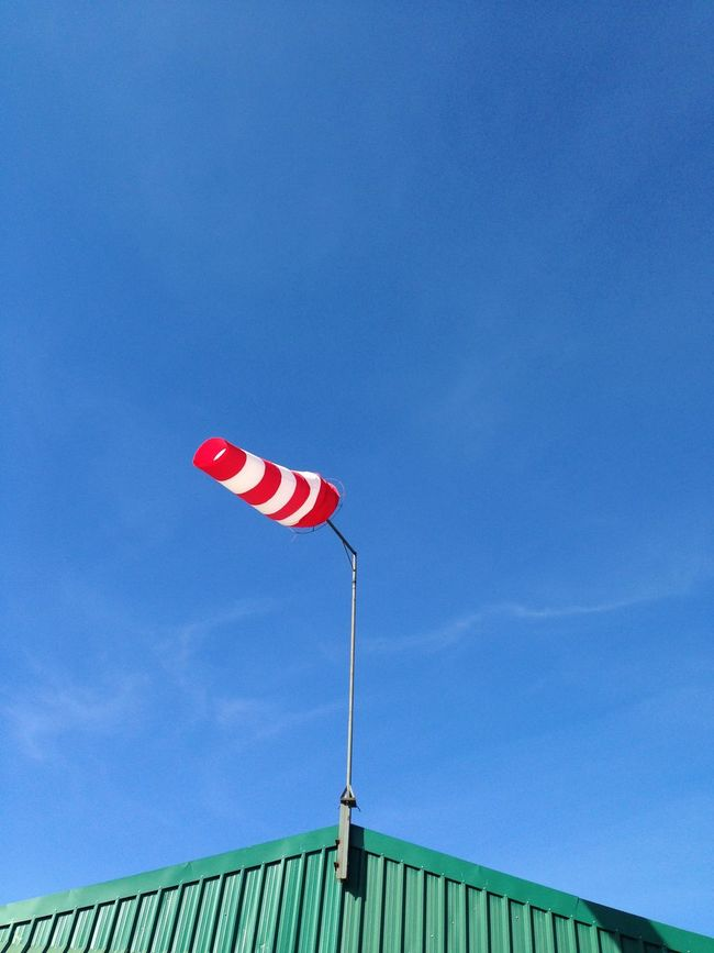 Airport Blue Flag Pole Fluttering Green Roof Hangar Low Angle View Outdoors Red White Stripes Sky Wind Wind Direction Wind Direction Indicator Windsack Windy