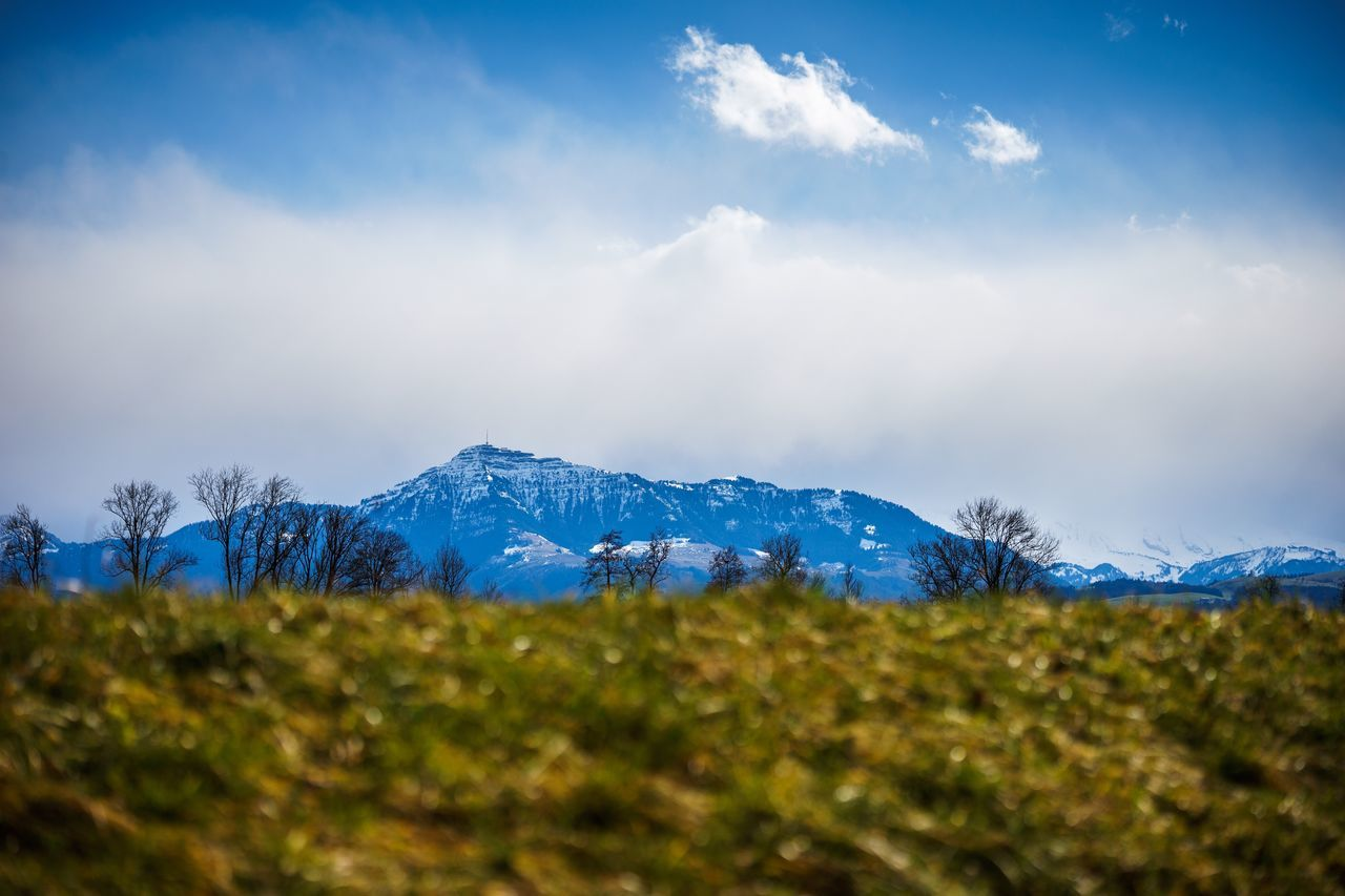mountain, beauty in nature, nature, sky, landscape, tranquility, tranquil scene, scenics, cloud - sky, blue, field, no people, outdoors, grass, day, snow, mountain range, cold temperature