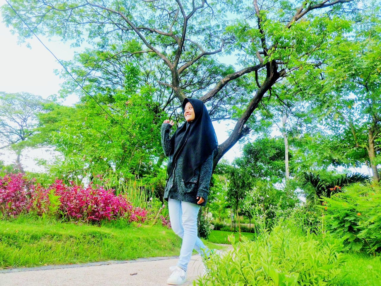 tree, one person, full length, real people, casual clothing, young adult, young women, growth, nature, front view, standing, day, plant, outdoors, leisure activity, flower, beautiful woman, lifestyles, grass, beauty in nature, people, adult