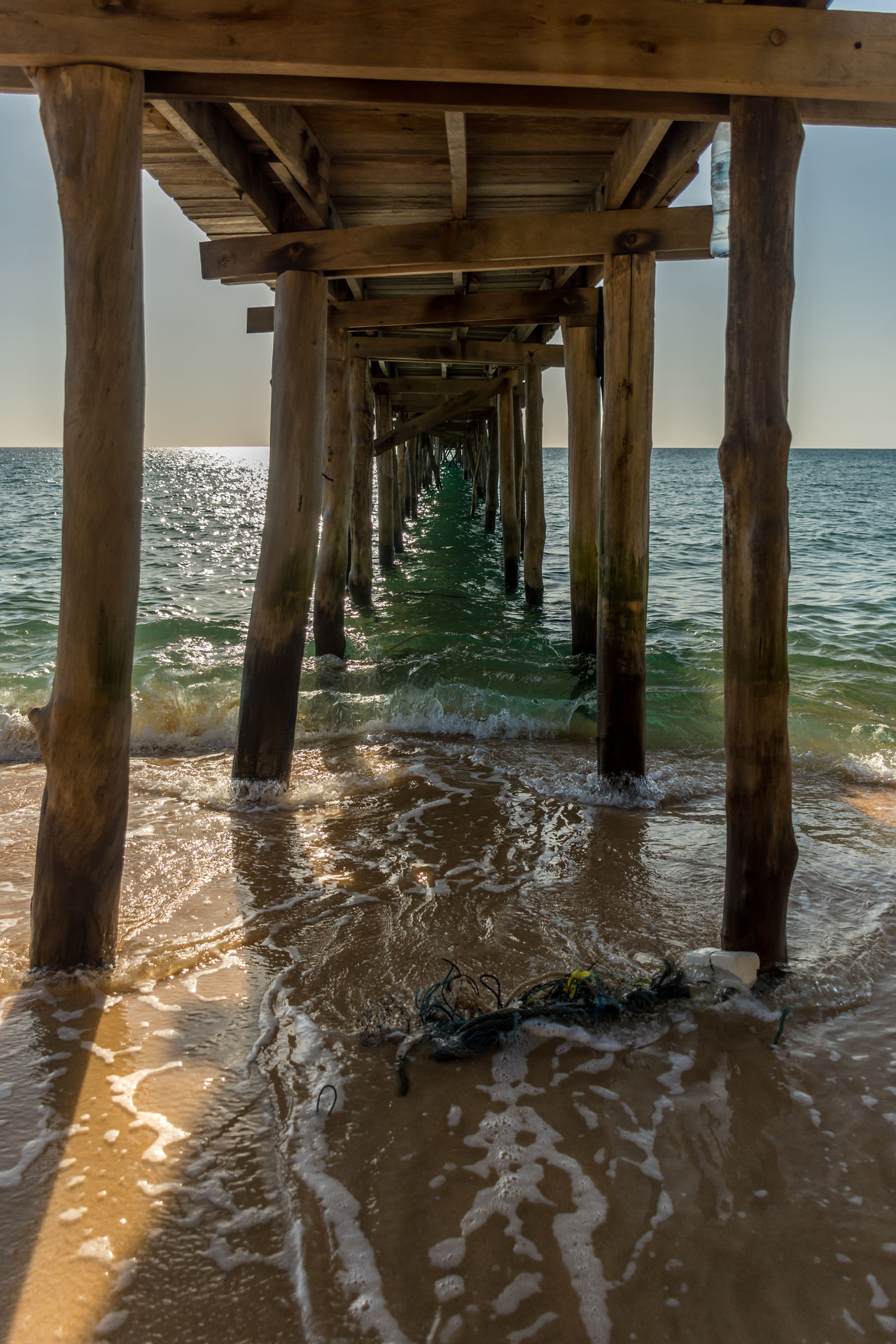 View under a old wooden jetty going out to sea from a golden sand beach. Beach Bridge - Man Made Structure Built Structure Calm Cambodia Golden Horizon Horizon Over Water Island Jetty Ocean Old Outdoors Pier Posts Rubbish Sand Sea Sun Tide Tranquil Scene Waves Wood Wood - Material Wooden