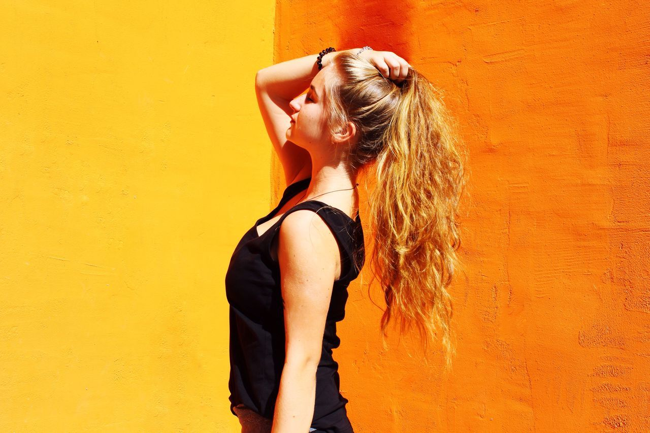 Full Length Of Young Woman Standing Against Yellow Wall