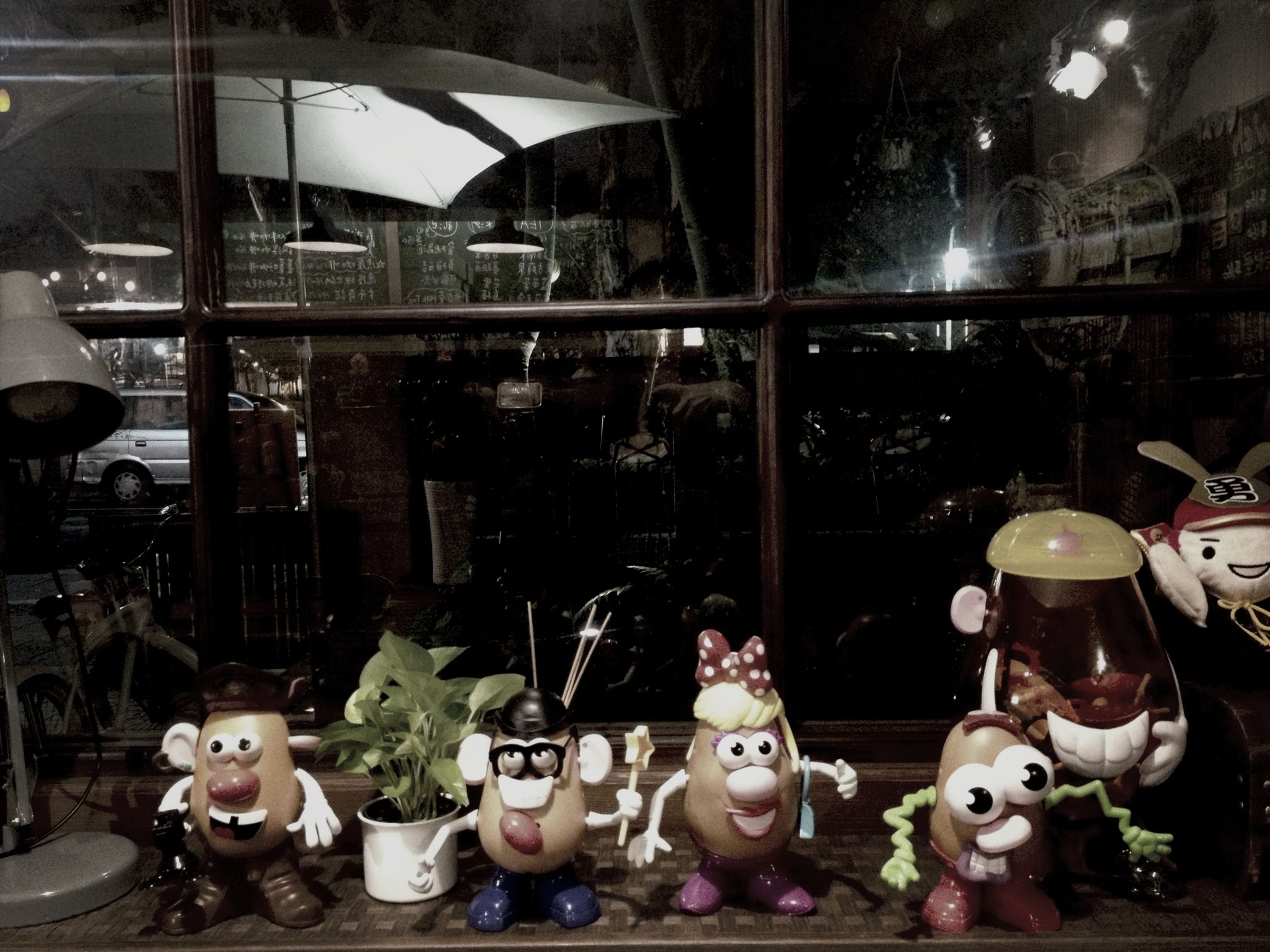 indoors, retail, large group of objects, store, human representation, glass - material, illuminated, for sale, choice, variation, shop, abundance, arrangement, still life, sitting, night, market, incidental people, retail display