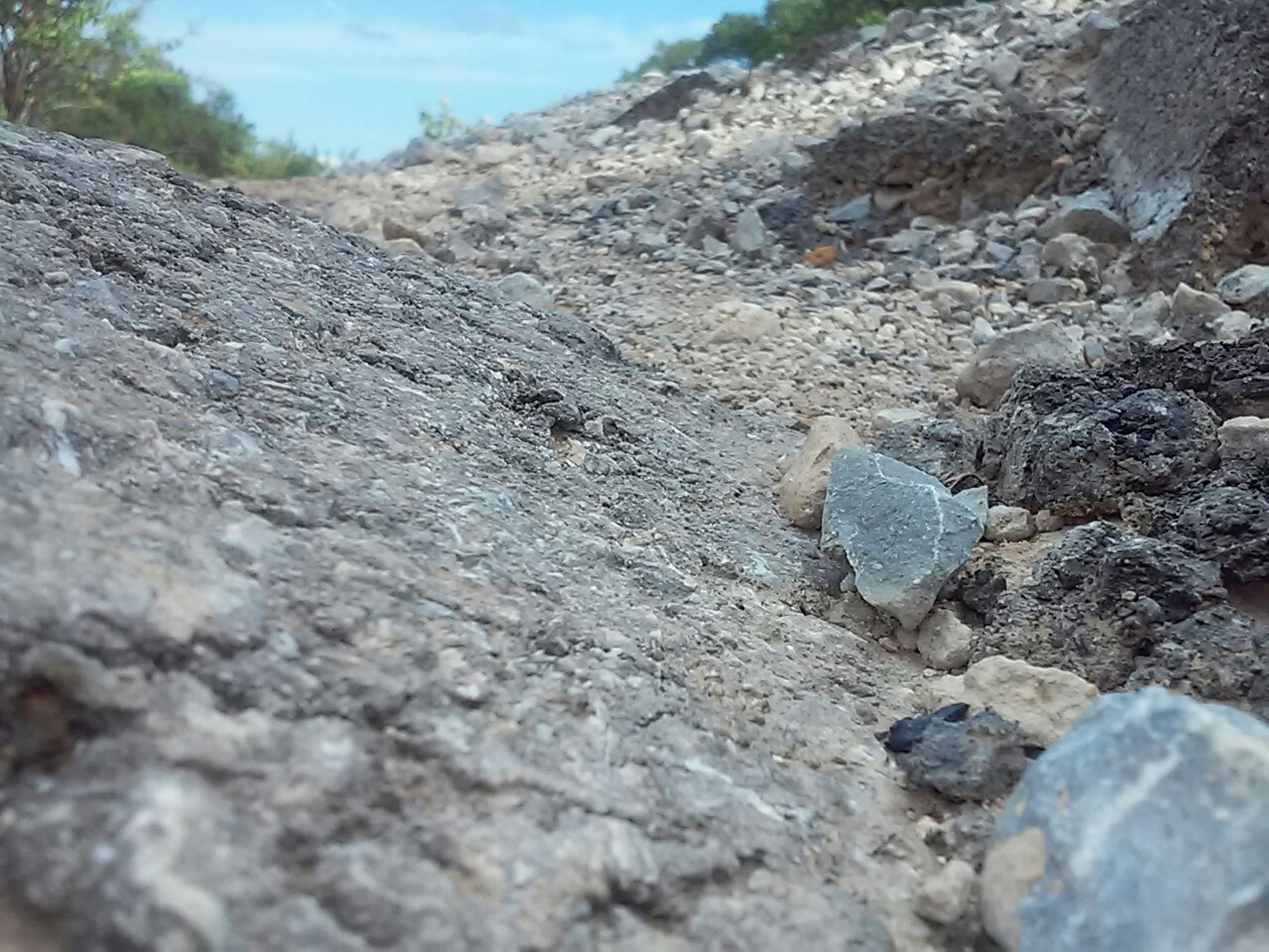 rock - object, textured, nature, tranquility, rough, rock formation, rock, beauty in nature, surface level, sky, tranquil scene, close-up, day, stone - object, outdoors, sunlight, mountain, scenics, stone, no people