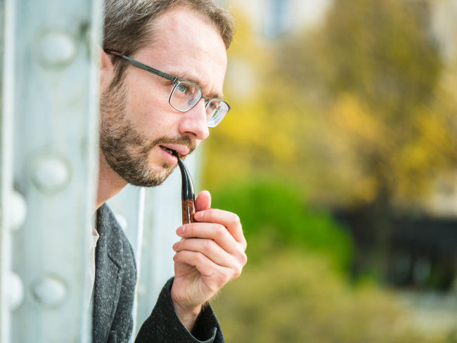 Handsomely dressed man with glasses smoking a pipe on the bridge in Paris Fashion Smoking Well-dressed Adult Adults Only Beard Casual Clothing Close-up Day Eyeglasses  Handsome Headshot Holding Lifestyles Men One Person Outdoors People Pipe Real People Young Adult