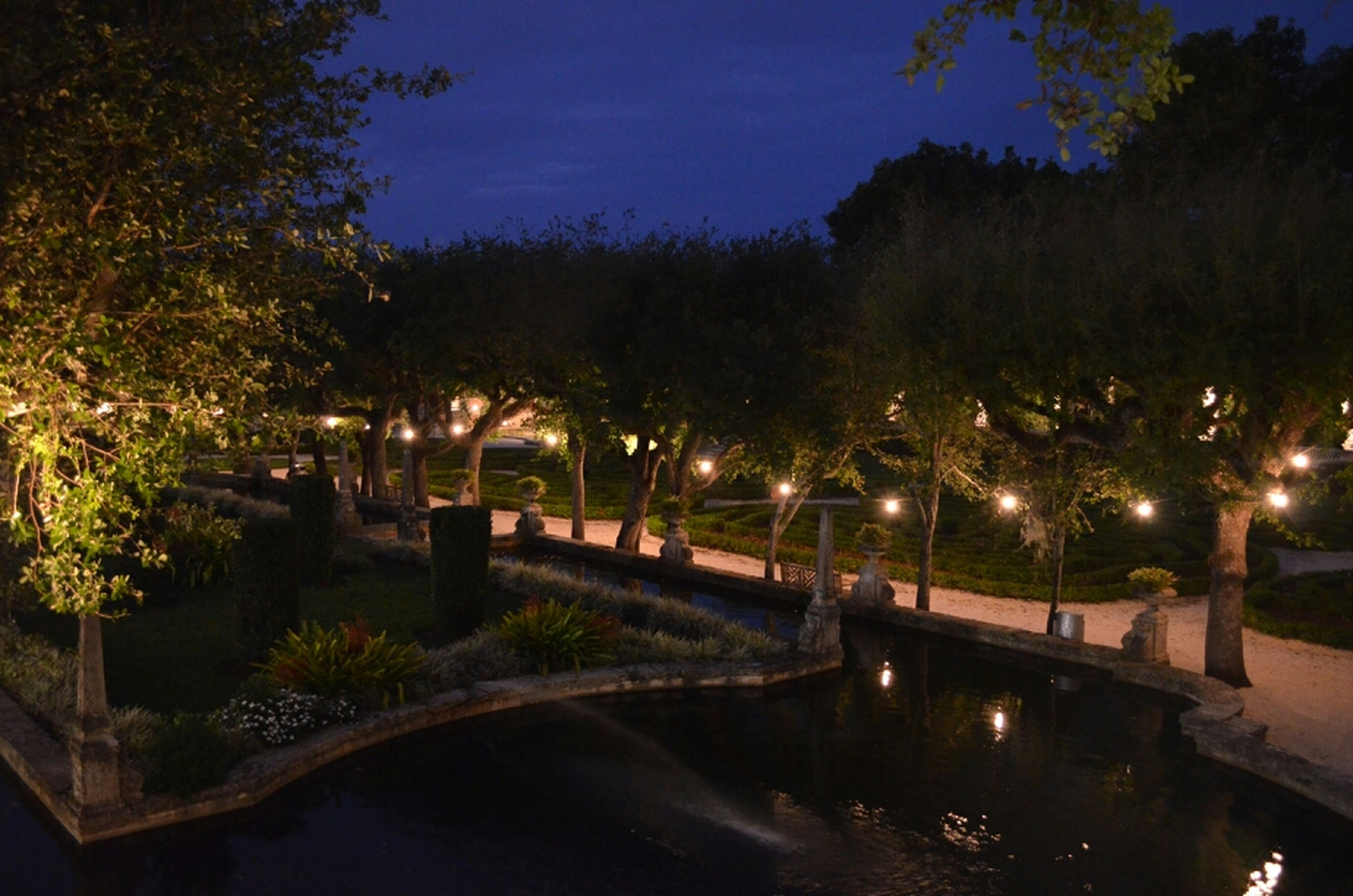 illuminated, water, tree, night, reflection, street light, river, tranquility, tranquil scene, sky, built structure, waterfront, nature, lighting equipment, scenics, beauty in nature, connection, bridge - man made structure, architecture, lake