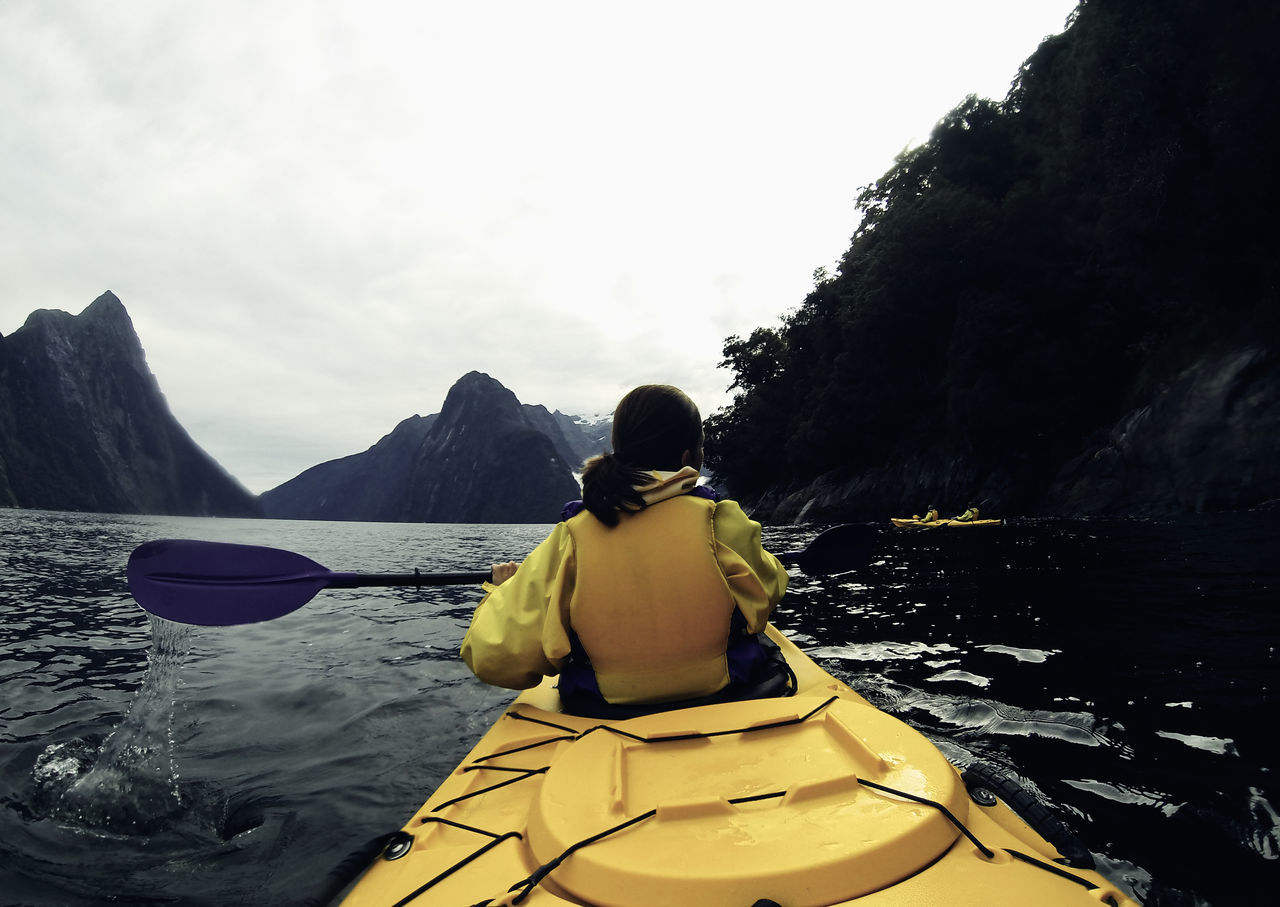 water, nature, nautical vessel, oar, day, tranquility, kayak, mountain, real people, river, beauty in nature, outdoors, one person, scenics, transportation, tranquil scene, rear view, leisure activity, yellow, lifestyles, sky, rowing, adventure, young adult, people