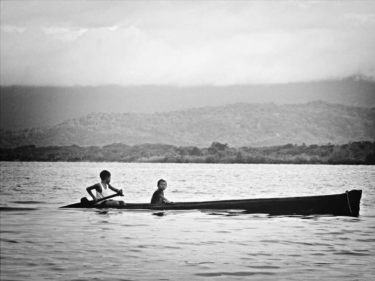 rowing, water, two people, men, oar, mountain, nautical vessel, sitting, real people, leisure activity, nature, sport rowing, day, sport, outdoors, sky, togetherness, sea, beauty in nature, sculling, adult, people, adults only