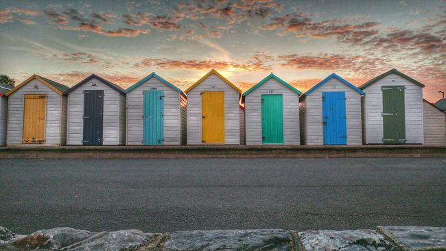 Beach huts at sunset on Preston Sands promenade, torbay Building Exterior Built Structure Architecture In A Row Window Sunset Multi Colored Cloud Sky Colorful Outdoors Repetition Façade Shore Cloud - Sky Exterior No People Sea Cloudy Surface Level Tourism Beach Water Waterfront Travel Destinations