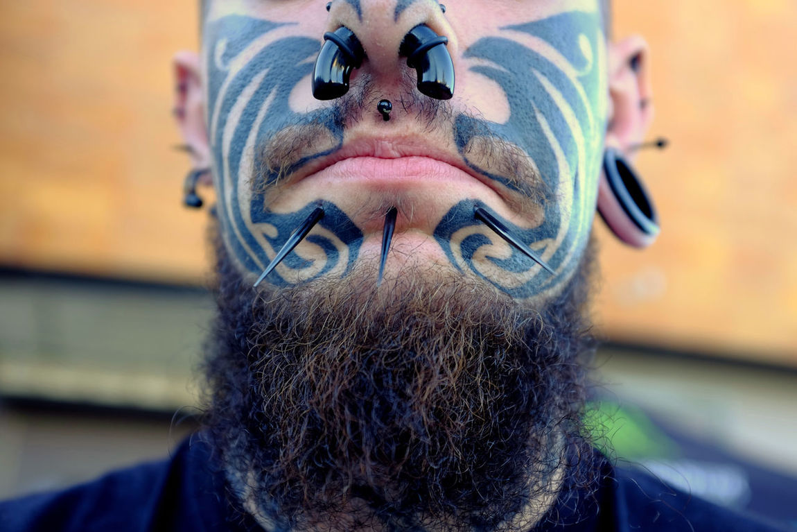 Close-up portrait of tatooed and pierced face young man. Beard Candid Caucasian Ethnicity Close-up Closeup Color Portrait Defocused Ear Piercings Face Lips Long Beard Male Man Mouth Nose Piercing Nose Ring Part Of Body Pierced Piercings Portrait Tatooed Tattoo The Portraitist - 2017 EyeEm Awards Young Adult