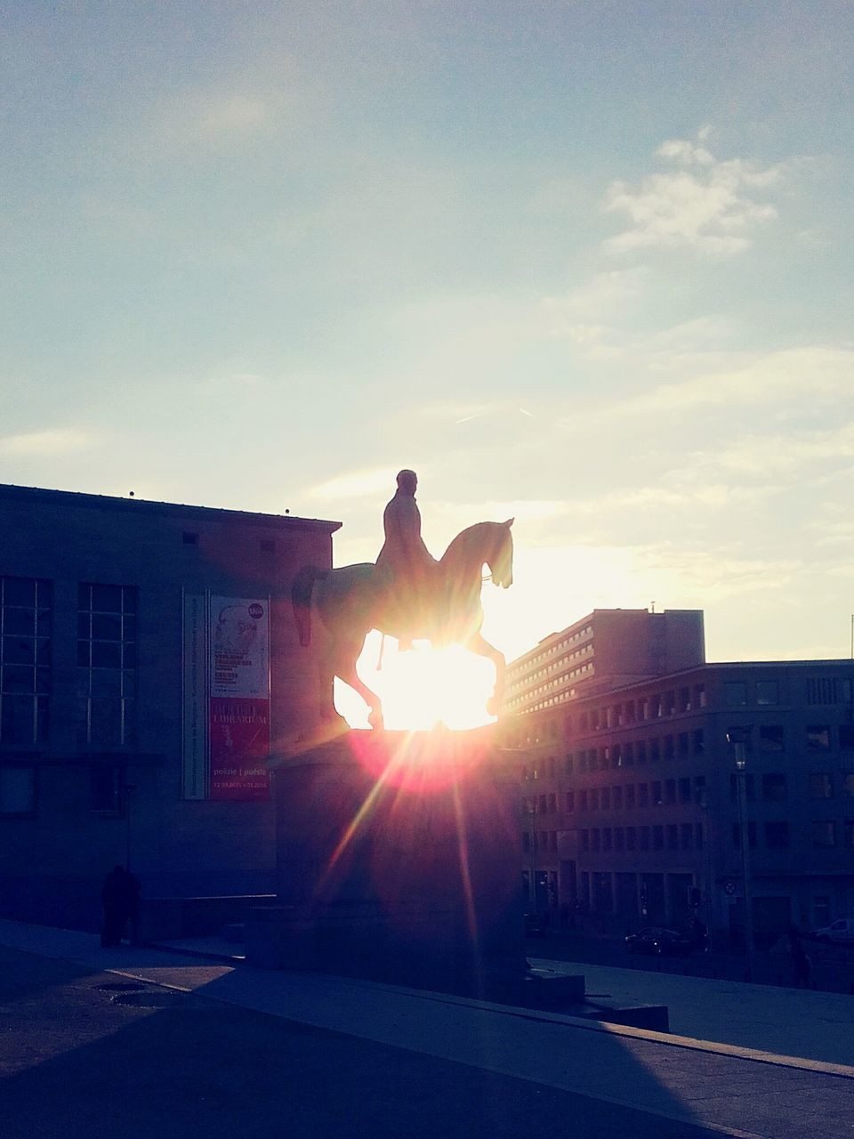 sunbeam, built structure, architecture, sunlight, building exterior, lens flare, real people, sky, sunset, sun, outdoors, one person, full length, leisure activity, silhouette, men, day, lifestyles, city, nature, people