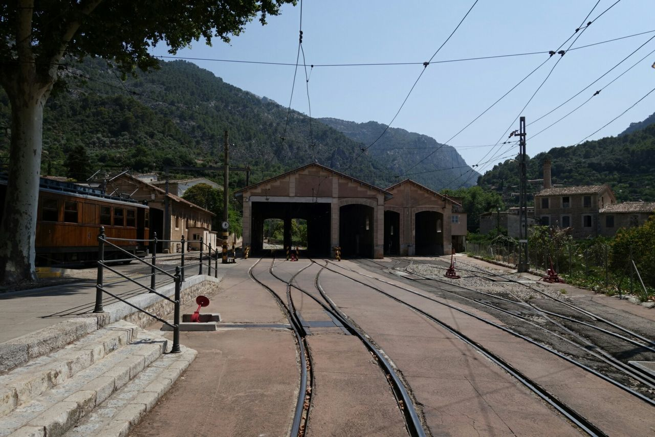 built structure, railroad track, transportation, architecture, cable, building exterior, rail transportation, tree, outdoors, mountain, day, the way forward, public transportation, sky, electricity pylon, real people, clear sky, nature