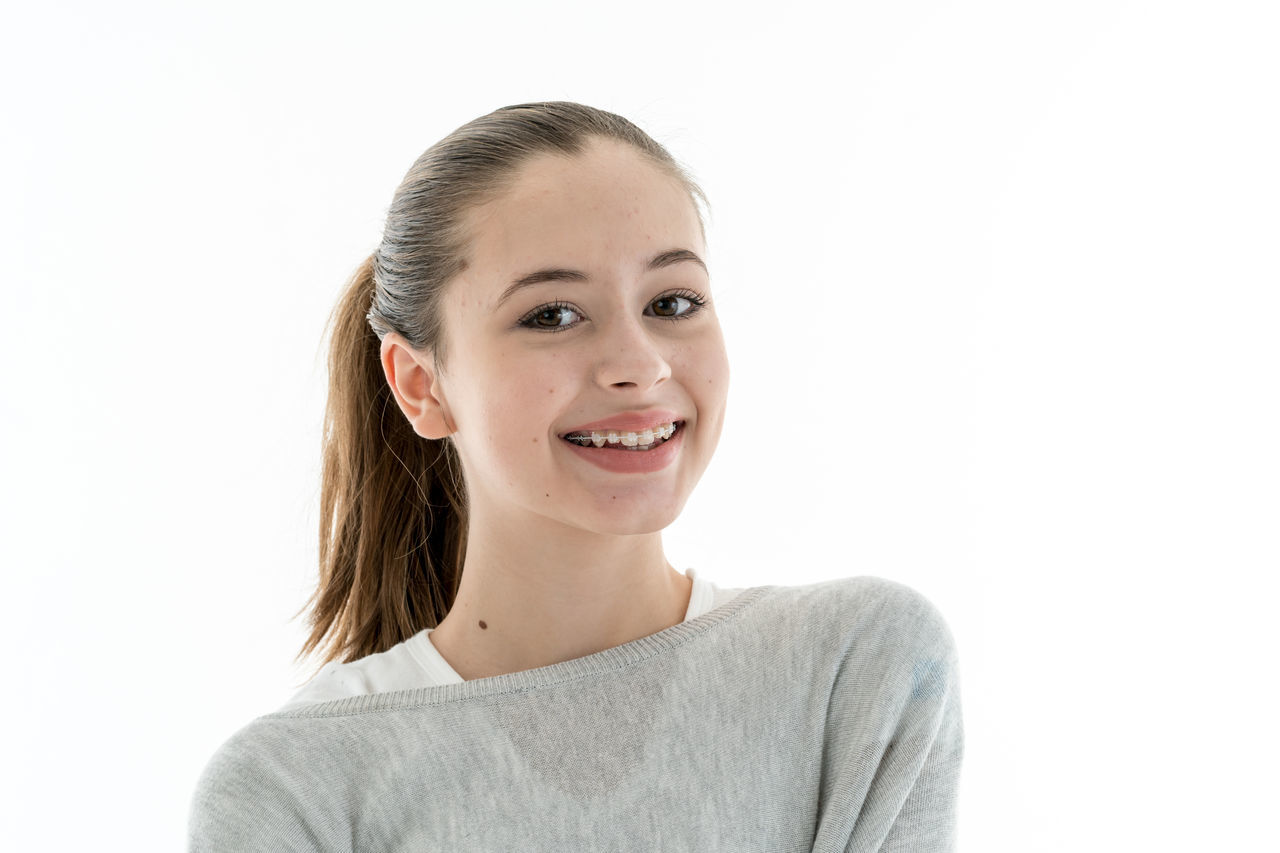Cute teenage girl with dental teeth braces Adolescent Beautiful People Beautiful Woman Beauty Cheerful Confidence  Dental Braces Front View Happiness Headshot Indoors  Looking At Camera One Person One Woman Only One Young Woman Only Portrait Smiling Studio Shot Teenage Girls Tooth Brace Toothy Smile White Background Young Adult The Portraitist - 2017 EyeEm Awards