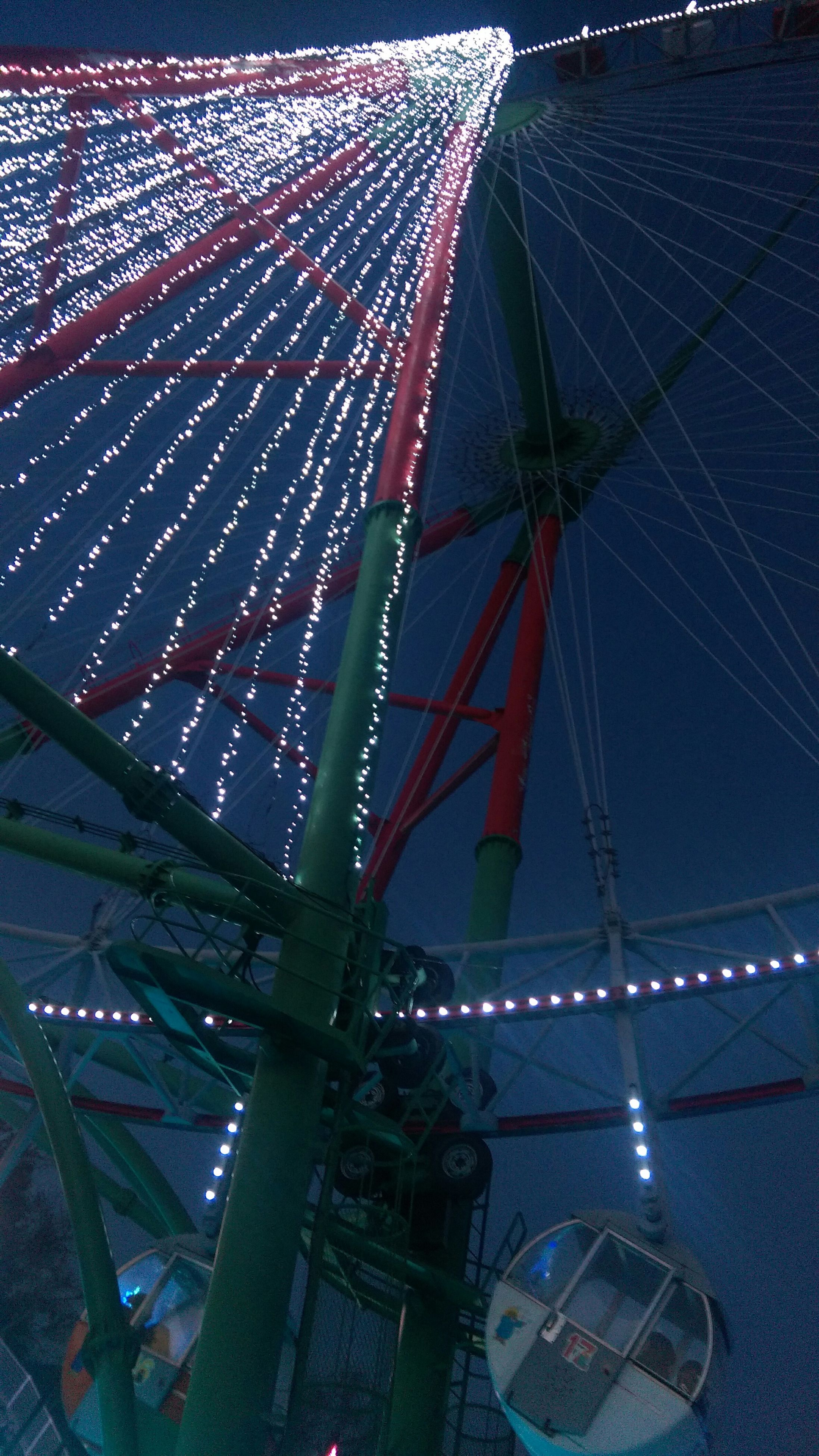 ferris wheel, night, illuminated, arts culture and entertainment, amusement park, amusement park ride, built structure, transportation, city, connection, architecture, outdoors, sky, bridge - man made structure, engineering, no people, high angle view, clear sky, multi colored, river