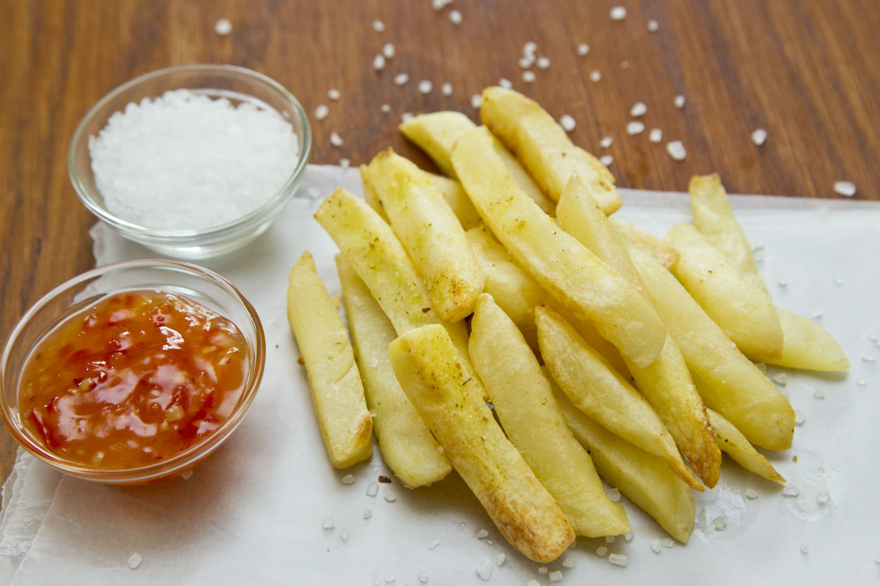 Tasty baked French fries on grease proof paper with salt and ketchup sauces Bowl Chilli Sauce Close-up Comfort Food Food French Fries Freshness Friends Indoors  No People Prepared Potato Ready-to-eat Salt Spices Unhealthy Eating