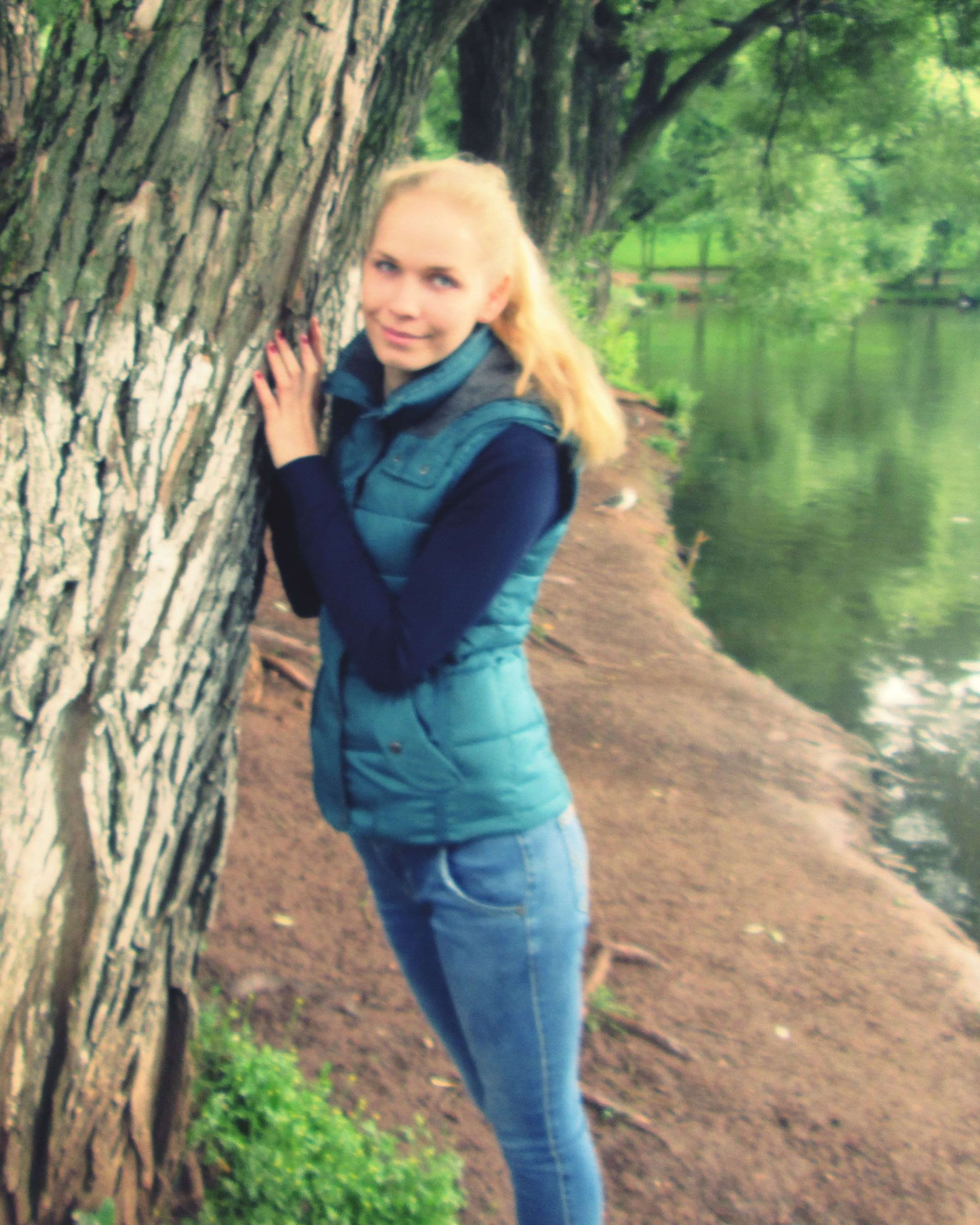 casual clothing, person, tree, lifestyles, standing, leisure activity, forest, young adult, portrait, looking at camera, three quarter length, front view, full length, smiling, tree trunk, nature, happiness, outdoors