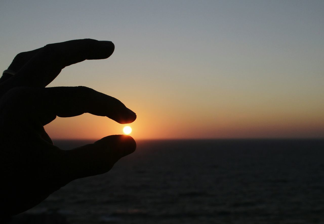 Optical Illusion Of Cropped Hand Holding Sun During Sunset