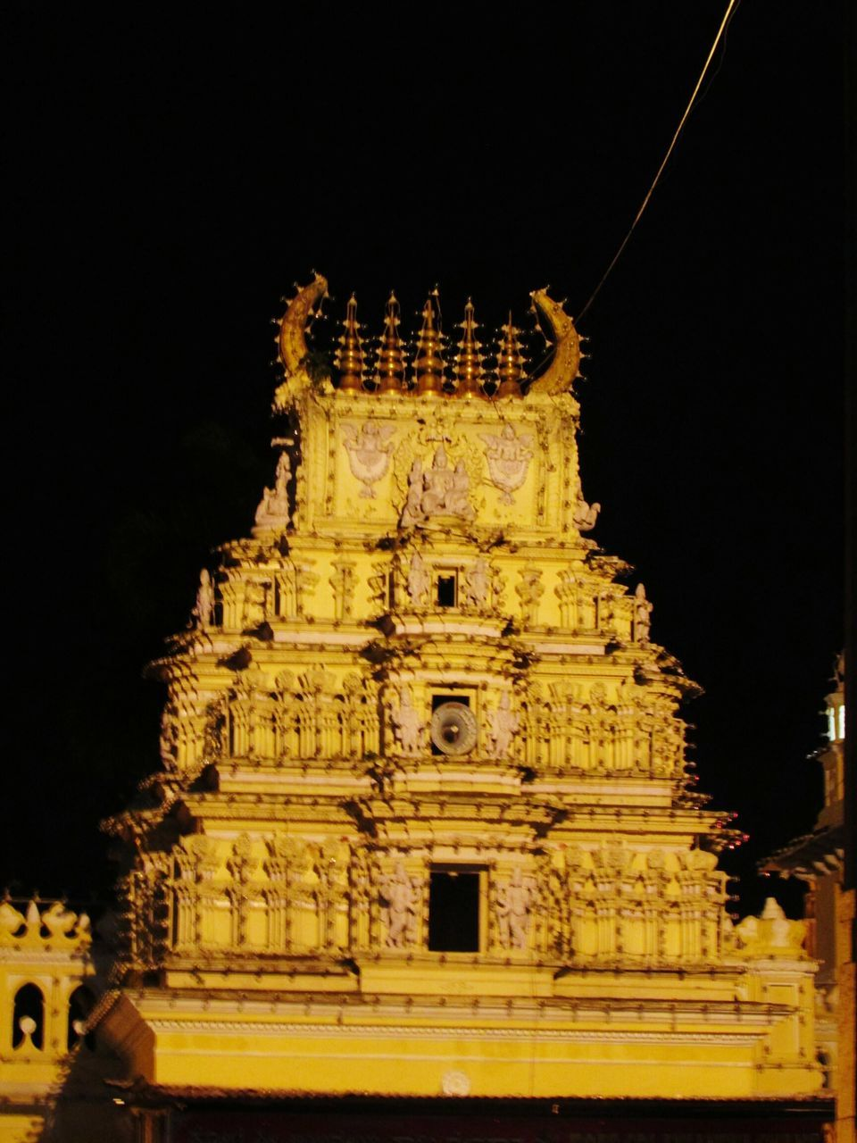 religion, spirituality, place of worship, statue, architecture, building exterior, sculpture, built structure, gold colored, history, travel destinations, low angle view, no people, illuminated, outdoors, night, sky