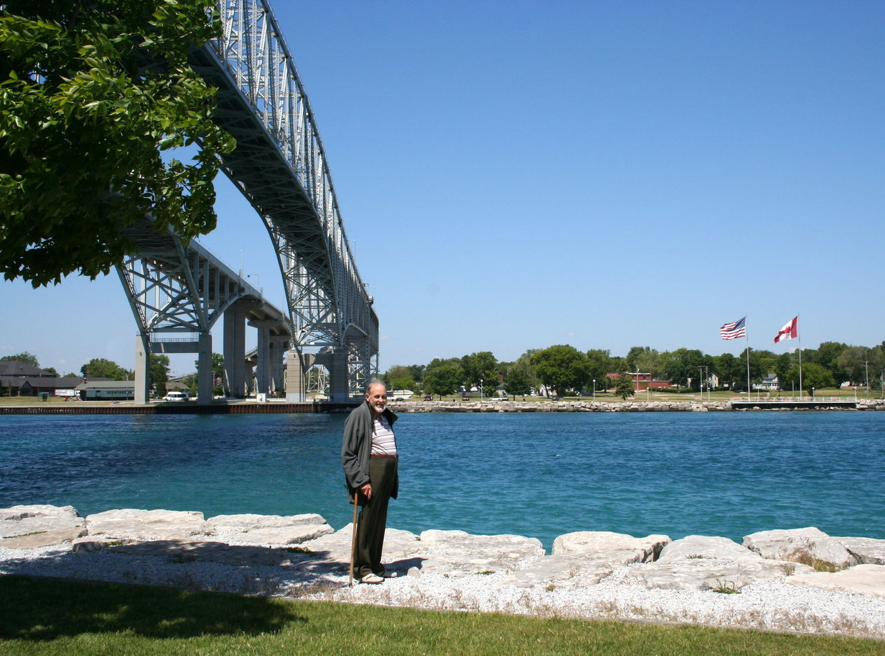 Caught On My Best Side ;) ~ Adult Architecture Blue Bridge - Man Made Structure Clear Sky Day Destination Flag Full Length My Best Side One Man Only One Person Outdoors People Photographer In The Shot Port Huron Sky St Clair River Sunlight Travel Destinations Tree Vacation Destination Vacations Visitor Water