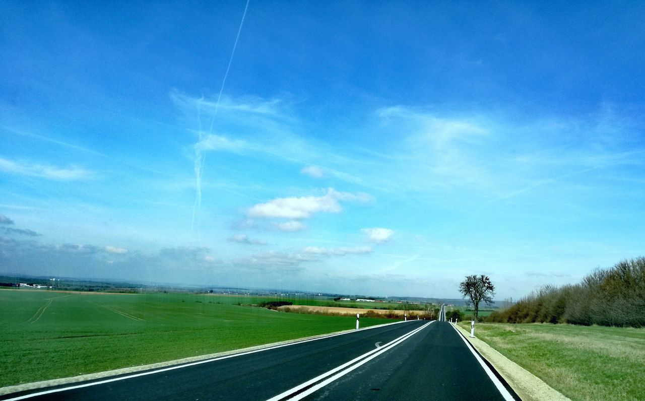 road, sky, transportation, the way forward, landscape, tranquil scene, blue, nature, no people, day, scenics, tranquility, field, beauty in nature, outdoors, cloud - sky, grass, vapor trail