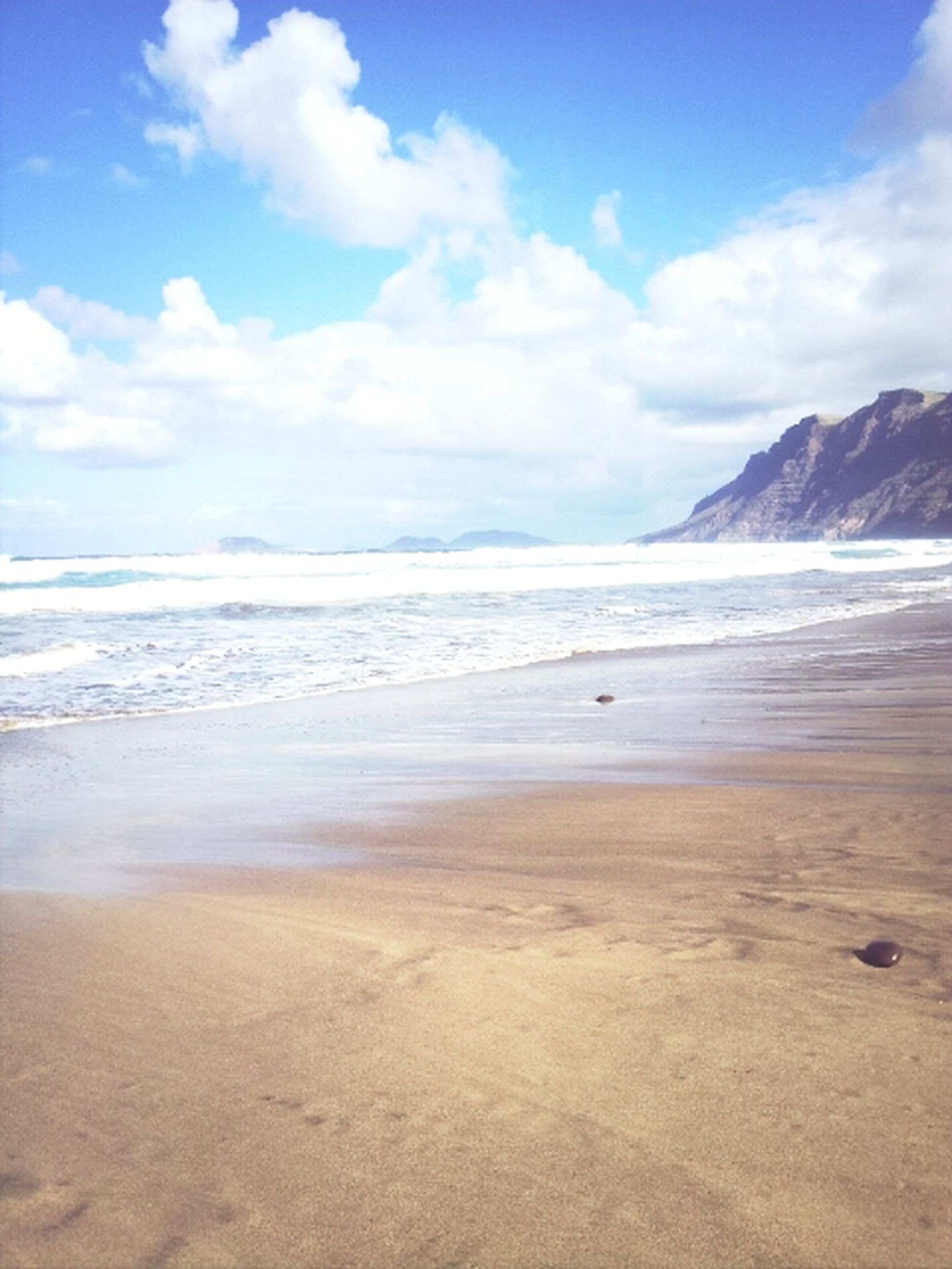 beach, sea, sand, sky, water, tranquil scene, tranquility, scenics, shore, beauty in nature, nature, mountain, cloud - sky, horizon over water, idyllic, cloud, coastline, wave, remote, day