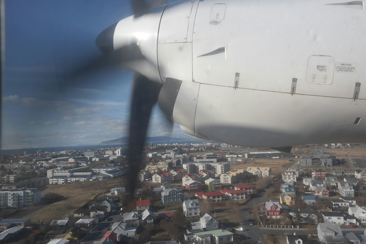 Cropped Image Of Airplane Flying Over City