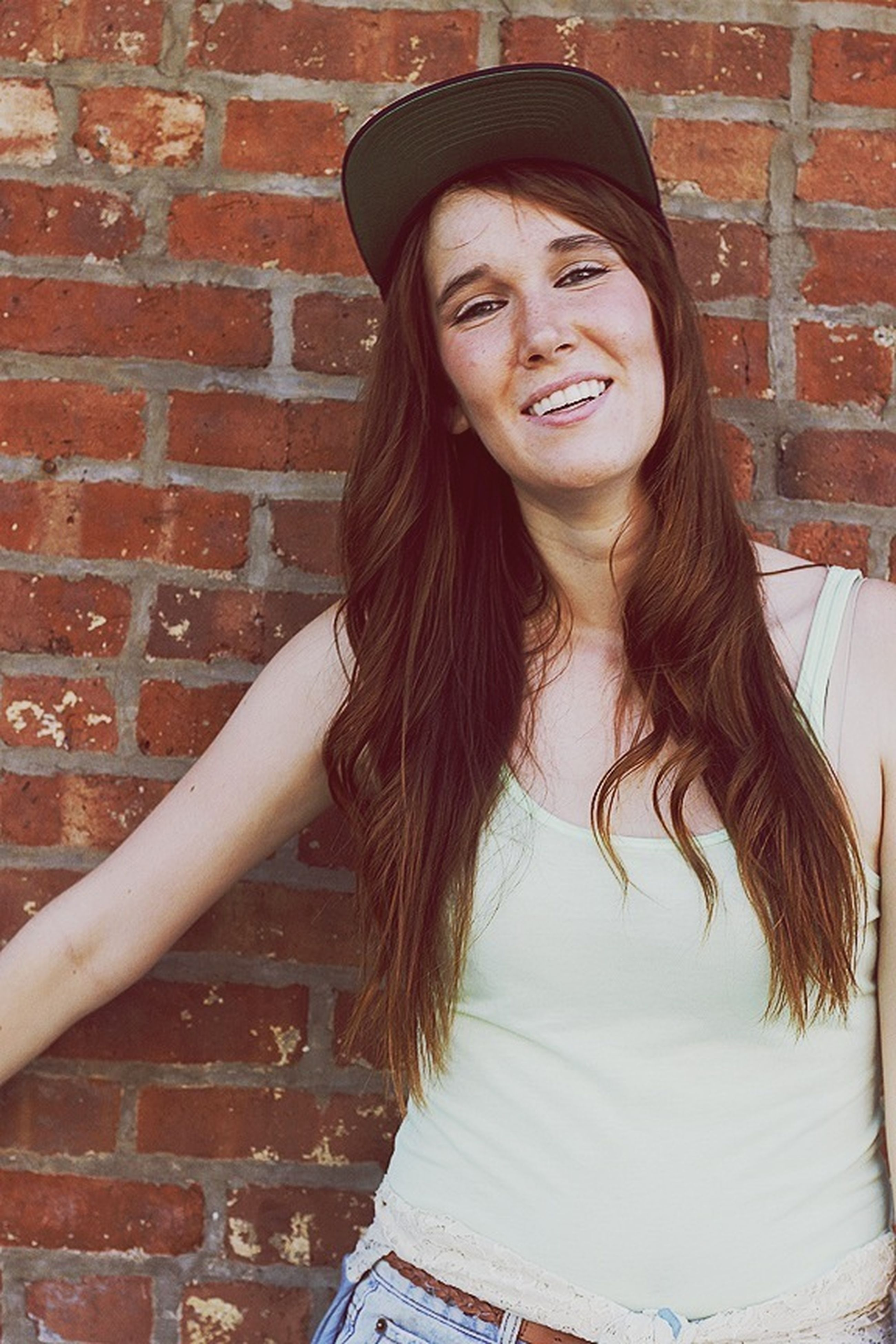 young adult, young women, long hair, portrait, looking at camera, lifestyles, person, front view, standing, casual clothing, brick wall, leisure activity, built structure, architecture, smiling, wall - building feature, beauty