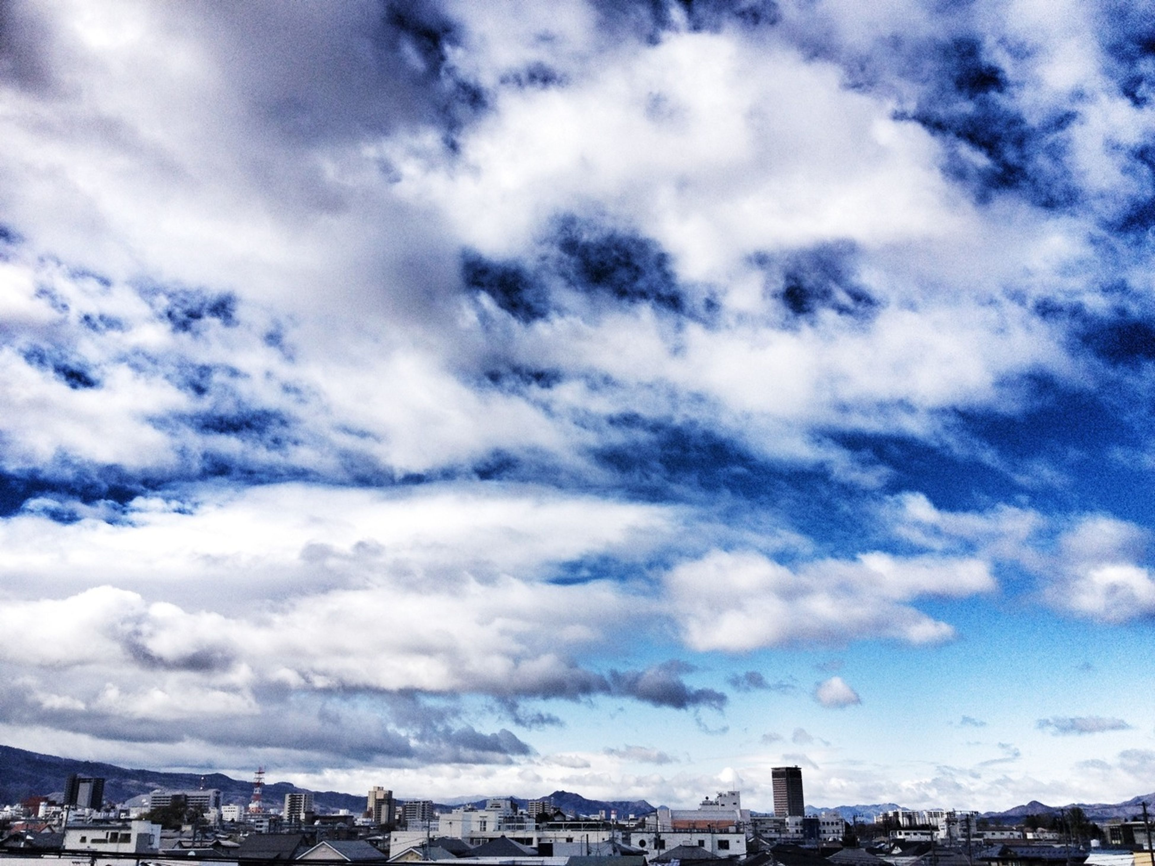 building exterior, architecture, built structure, city, cityscape, sky, cloud - sky, crowded, cloudy, residential district, cloud, residential building, blue, city life, weather, residential structure, day, high angle view, outdoors, no people