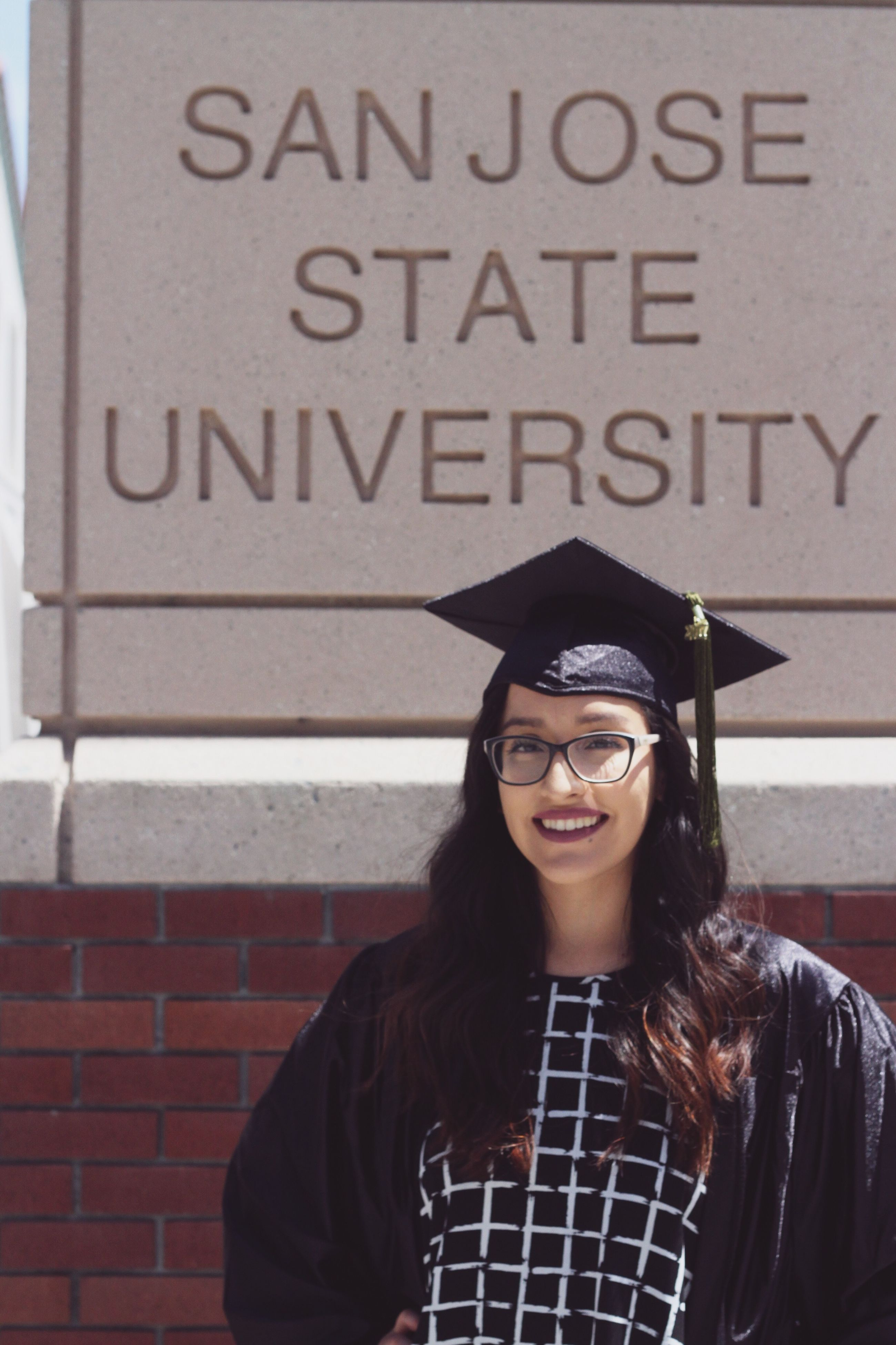 text, western script, communication, looking at camera, front view, real people, young adult, education, graduation, young women, happiness, portrait, lifestyles, smiling, one person, standing, day, outdoors, university student