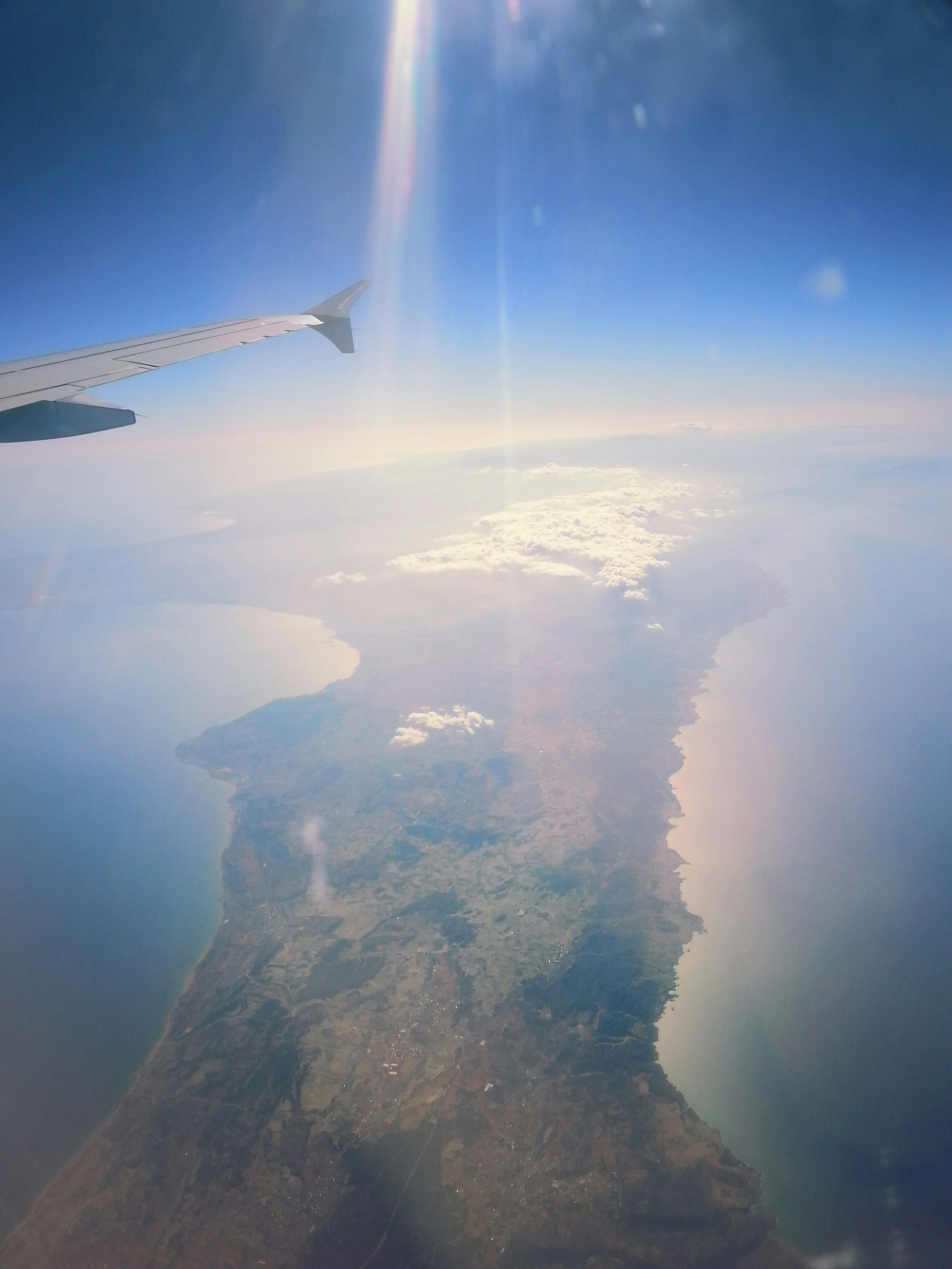scenics, sea, beauty in nature, aerial view, tranquil scene, sky, flying, water, tranquility, nature, blue, horizon over water, idyllic, sunbeam, sunlight, airplane, mid-air, landscape, cloud - sky, mountain