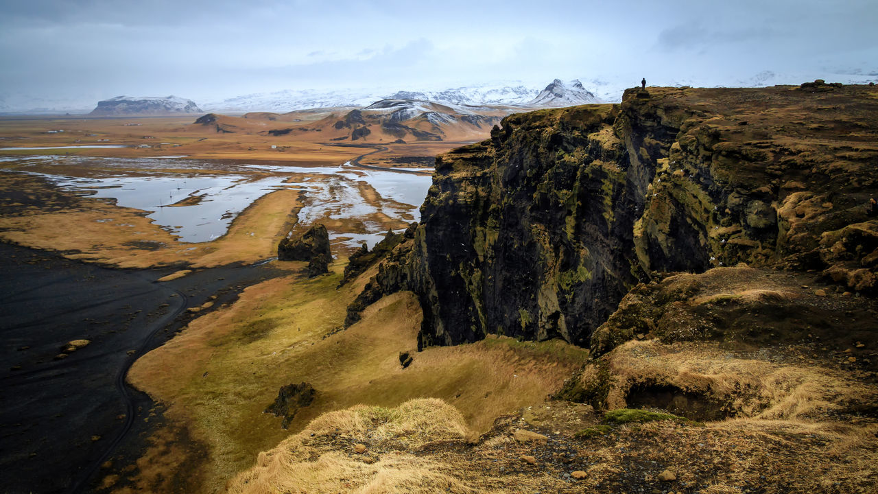 Looking northwest from the top of Dyrholaey in Iceland Dyrhólaey Grass Iceland Panoramic Vista Adventure Beauty In Nature Black Beach Cold Temperature Conquering Adversity Day Dramatic Weather Landscape Mountain Muted Colors Nature One Person Outdoors Scenics Sky Tranquil Scene Tranquility
