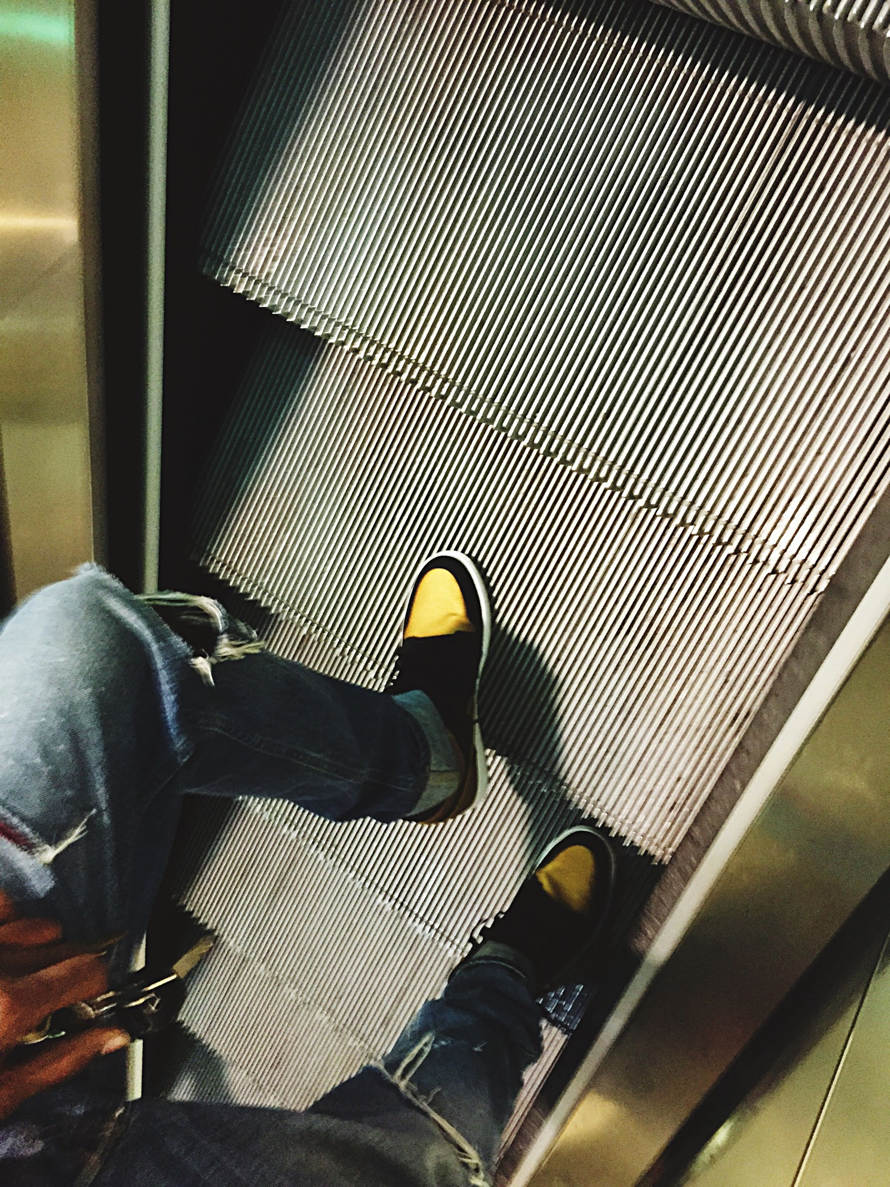 indoors, low section, person, shoe, lifestyles, men, high angle view, personal perspective, escalator, human foot, jeans, sitting, footwear, standing, relaxation, leisure activity, vehicle seat